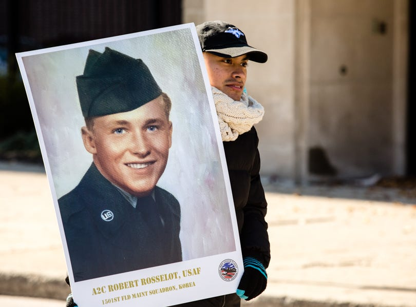A man holds a photo in the Veterans Day Parade.