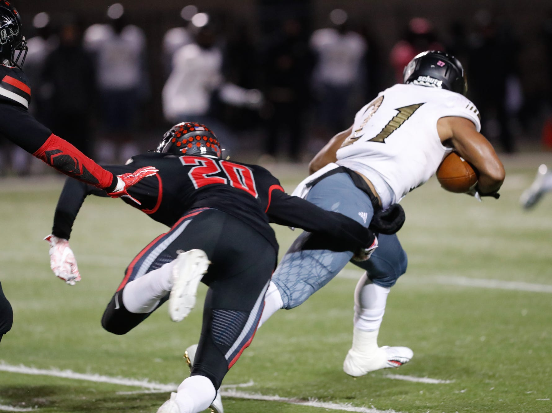 Warren Central High School Warriors Romeir Elliott (21), carries the ball past the North Central High School Panthers free safety Michael Brown (20), during a regional finals game at North Central High School on Friday, Nov. 9, 2018.