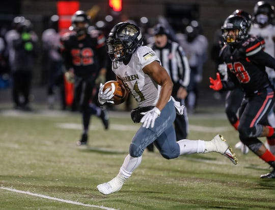 The Warren Central High School Warrior's Romeir Elliott (21), carries the ball for a touchdown during a regional finals game against the North Central High School Panthers, at North Central High School on Friday, Nov. 9, 2018.