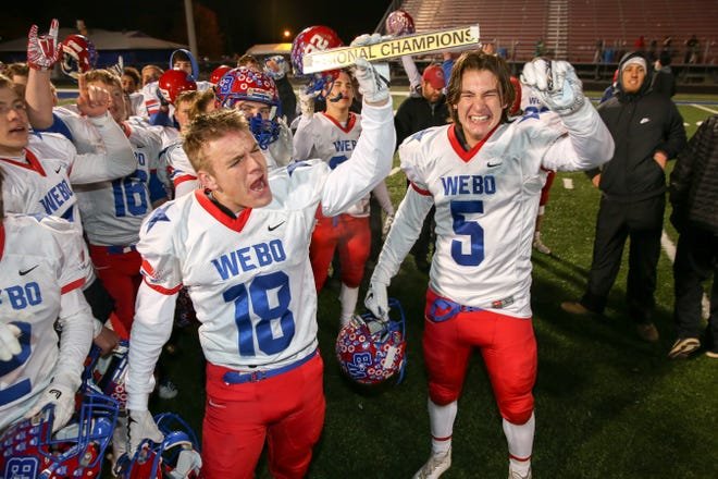 Western Boone's Peyton Young (18) proudly displays the Regional Championship trophy after their 19-7 victory in the Indianapolis Scecina vs Western Boone High School varsity football in the Class 2A Regional Championship held at Roncalli High School, Friday, November 9, 2018.