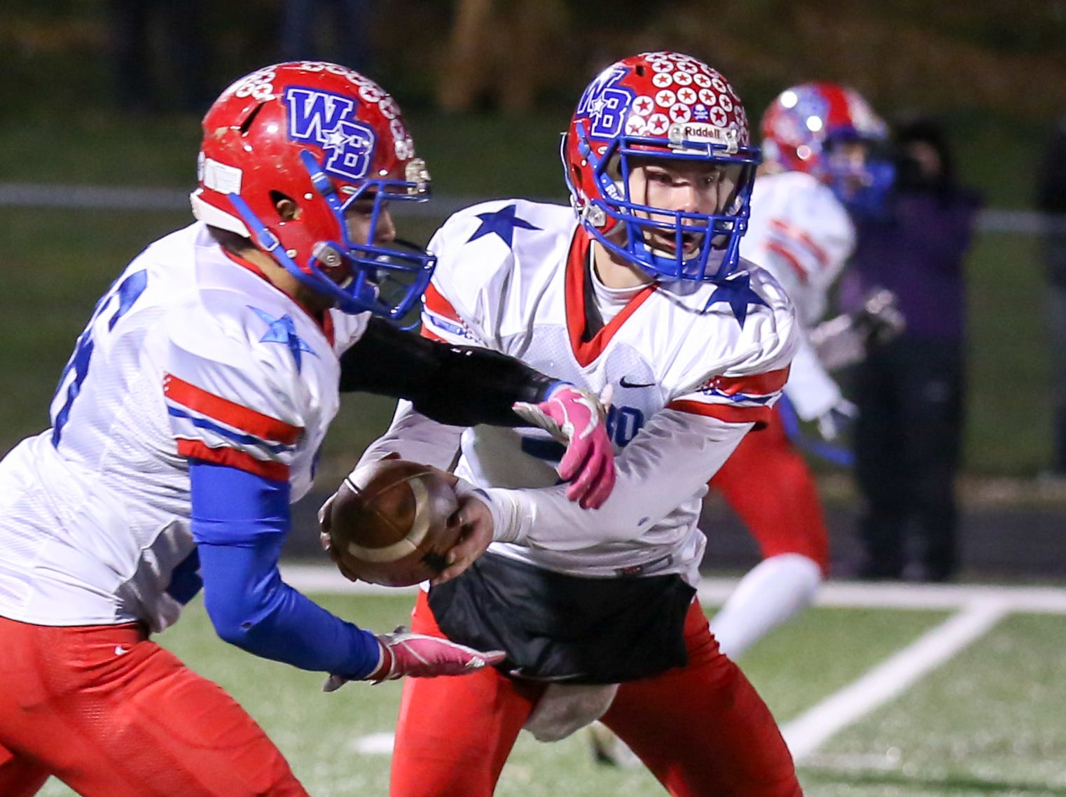 Western Boone's Spencer Wright (7)  hands off to Western Boone's Kruze Washingto (36) during the first half of Indianapolis Scecina vs Western Boone High School varsity football in the Class 2A Regional Championship held at Roncalli High School, Friday, November 9, 2018.