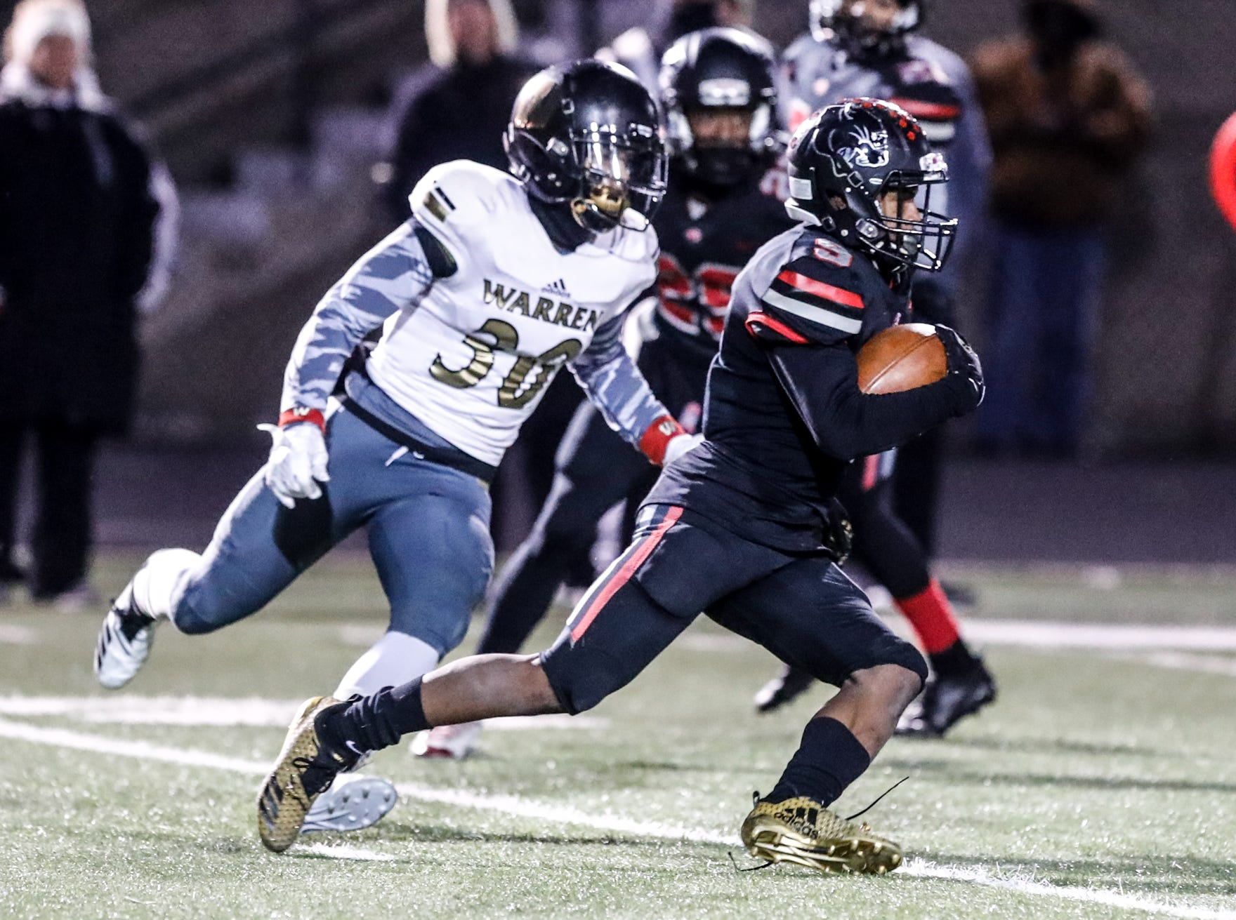 North Central High School Panthers Tre'von Elliott (9), outruns Warren Central High School Warrior's Calum Carruthers (30), for an 85 yard touchdown during a regional finals game at North Central High School on Friday, Nov. 9, 2018.