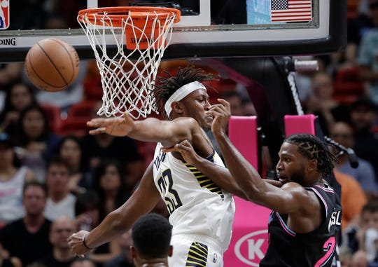 Miami Heat forward Justise Winslow, right, passes the ball as Indiana Pacers center Myles Turner (33) defends during the first half of an NBA basketball game Friday, Nov. 9, 2018, in Miami.