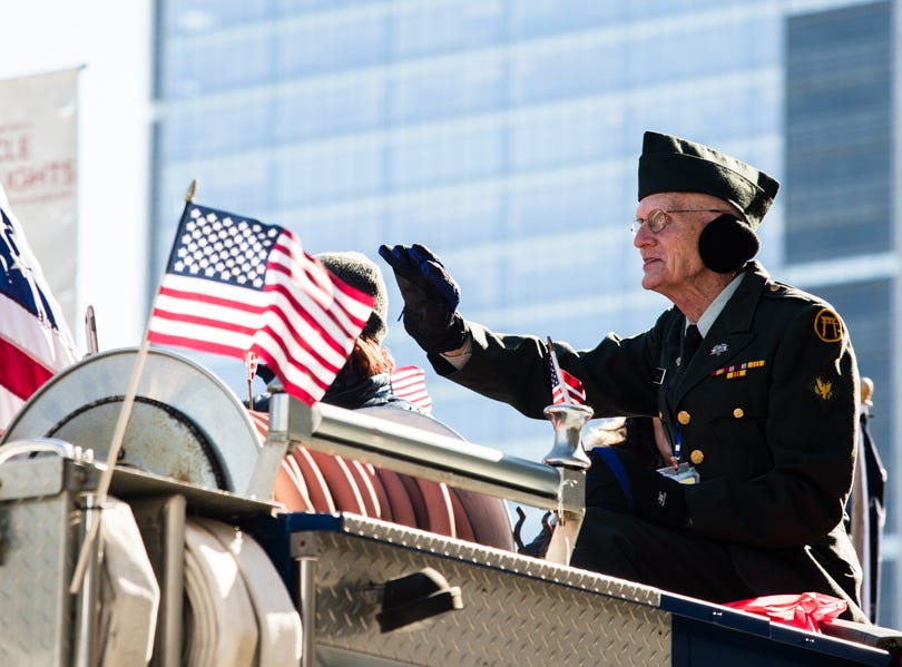 A veteran hoists a salute during the Indianapolis Veterans Day Parade.