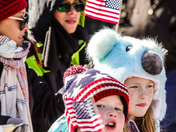 Kids wave flags in the Veterans Day Parade.