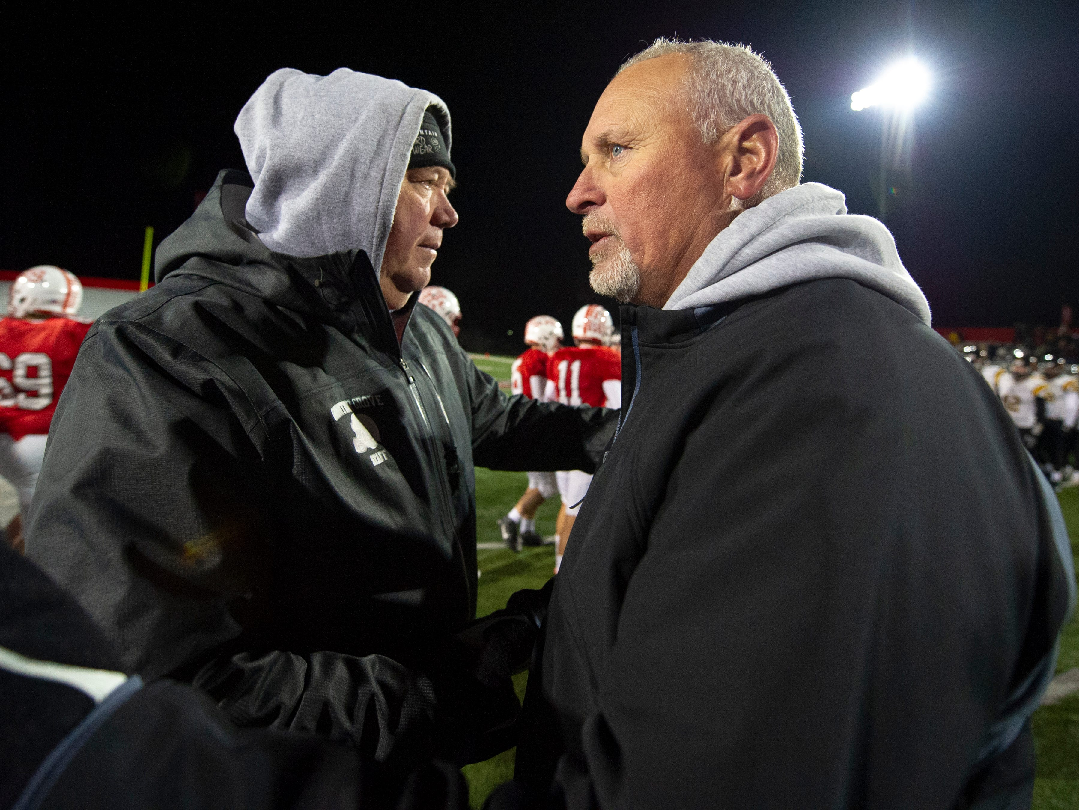 Center Grove High School head coach Eric Moore, left, and Avon High School head coach Mark Bless meet on the field after the game. Center Grove High School hosted Avon High School in an IHSAA Class 6A Regional Championship varsity football game, Friday, Nov. 9, 2018. Center Grove won 17-0 to advance to semi-state.