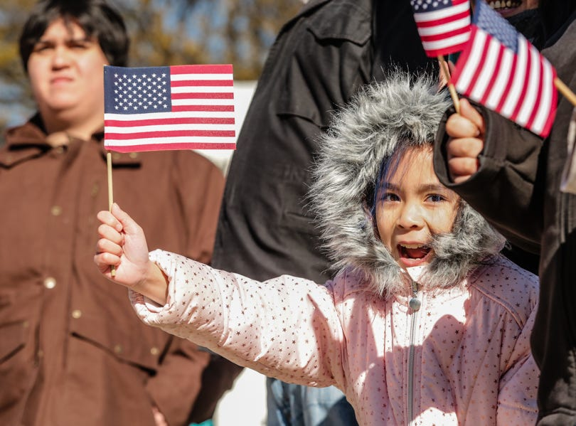 A girl cheers on the Veterans Day Parade while waving a flag.