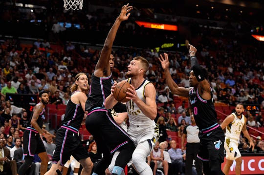Indiana Pacers forward Domantas Sabonis (11) drives the ball around Miami Heat center Hassan Whiteside (21) during the first half at American Airlines Arena.
