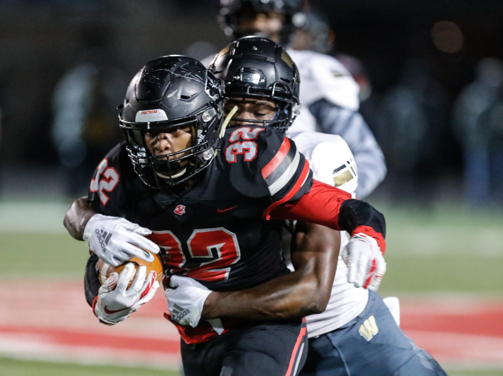 The North Central High School Panther's running back Alexander Tarver (32), is tackled by Warren Central High School Warrior's Frederick Talley (1), during a regional finals game against the Warren Central High School Warriors at North Central High School on Friday, Nov. 9, 2018.