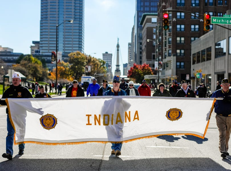 Members of the American Legion walk banner down Meridian Street during the Veterans Day Parade.