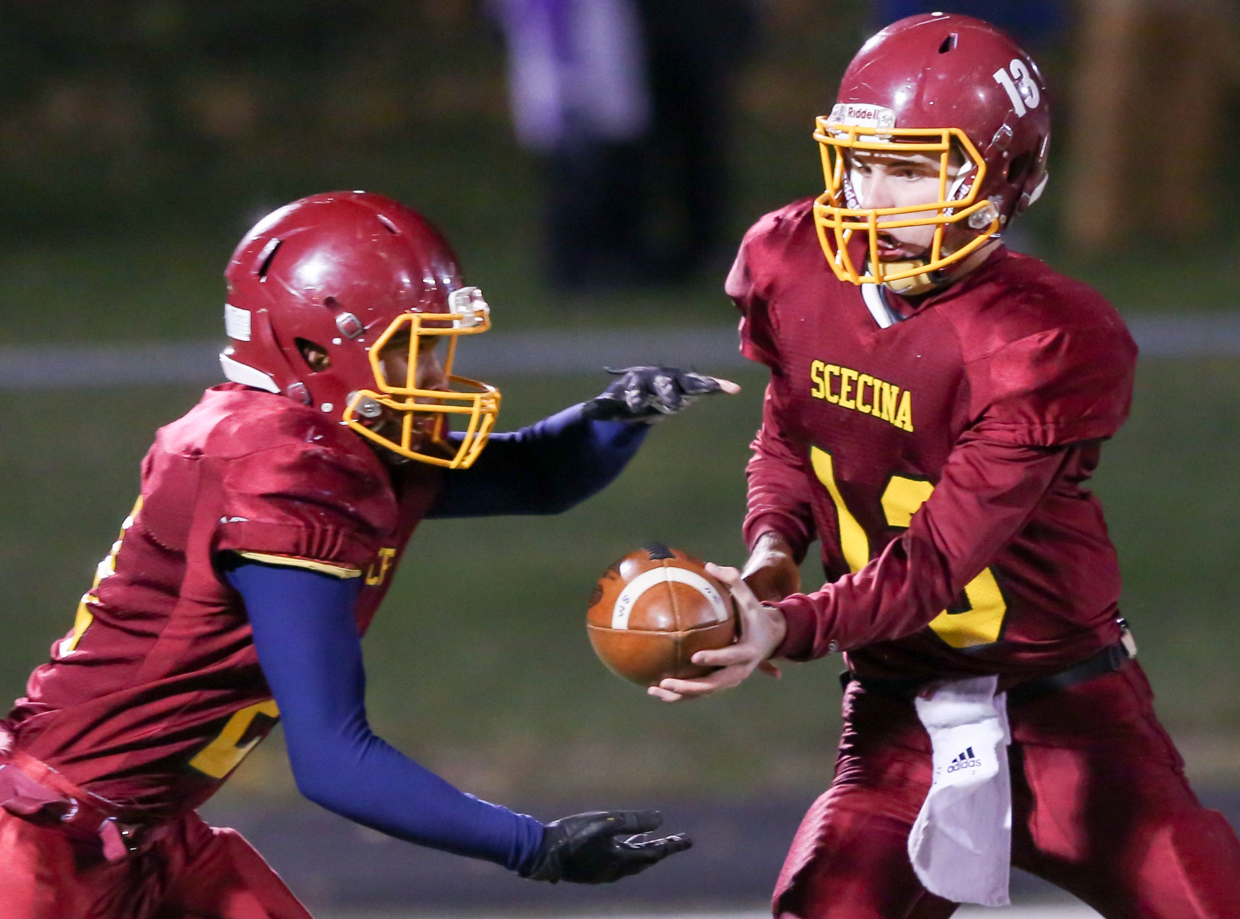 Scecina's Mac Ayres (13)  hands the ball off to Scecina's Tavon Middlebrook (21) during the first half of Indianapolis Scecina vs Western Boone High School varsity football in the Class 2A Regional Championship held at Roncalli High School, Friday, November 9, 2018.