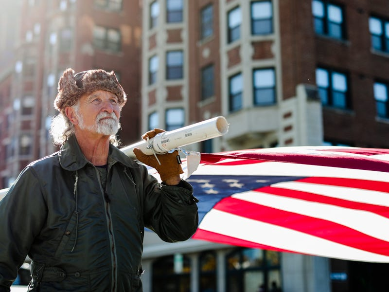 A man carries a large American Flag during the Veterans Day Parade downtown on Saturday.