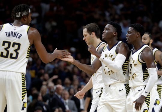 Indiana Pacers guard Victor Oladipo, second from right, is congratulated by center Myles Turner (33) during the second half of the team's NBA basketball game against the Miami Heat, Friday, Nov. 9, 2018, in Miami. The Pacers won 110-102.