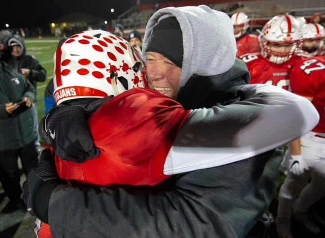 Center Grove coach Eric Moore celebrate the team's victory with his son, senior quarterback Jack Moore (1) after the game. Center Grove High School hosted Avon High School in an IHSAA Class 6A Regional Championship varsity football game, Friday, Nov. 9, 2018. Center Grove won 17-0 to advance to semi-state.