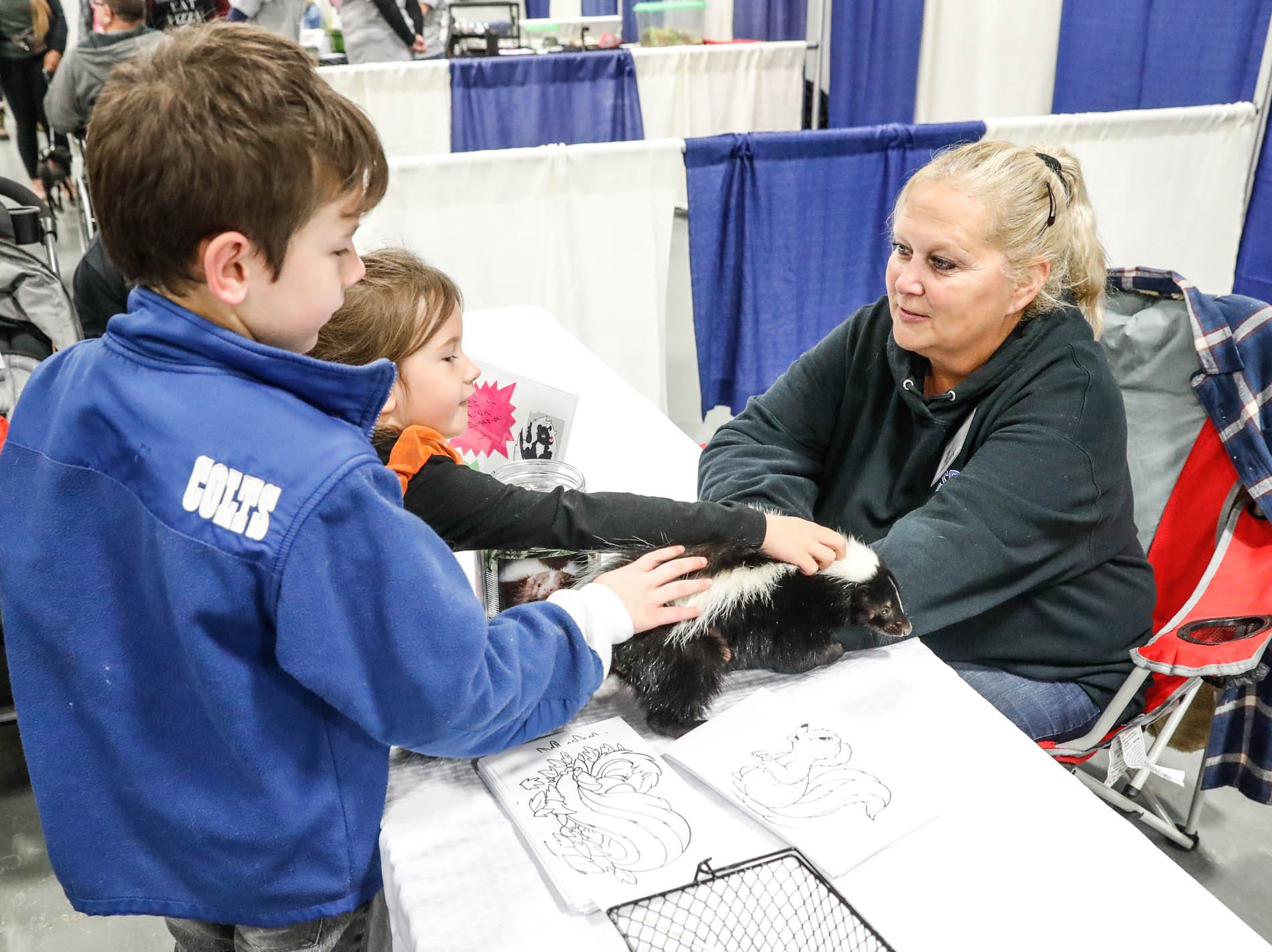 Drake and Charlotte Lewis get a chance to pet Diana, a young skunk belonging to Julie McLaughlin, right, from the Indiana Skunk Rescue at the Great Indy Pet Expo, held at the Indiana State Fairgrounds on Sat. Nov. 10, 2018.