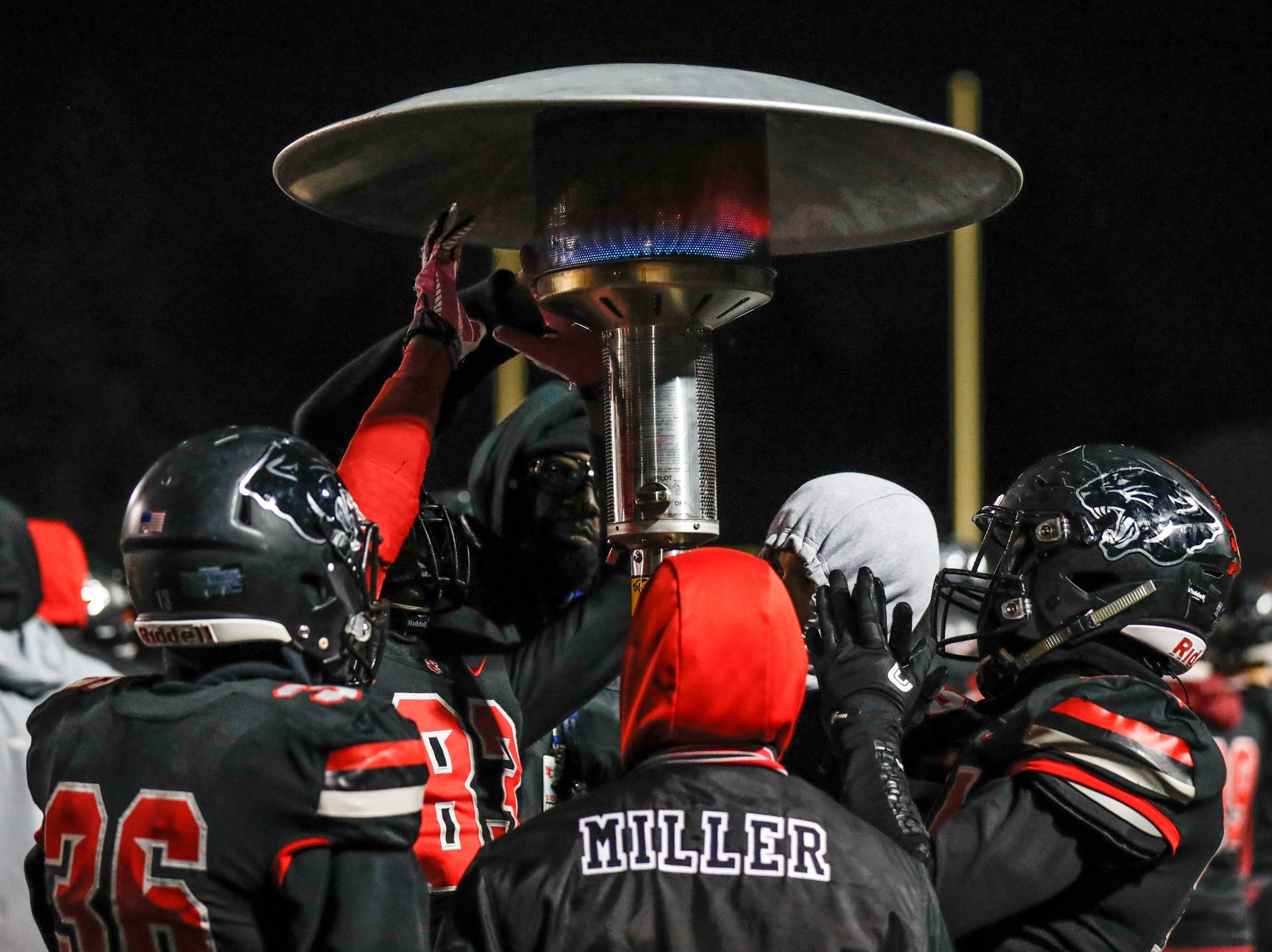 North Central High School Panthers football players warm their hands  during a regional finals game against the Warren Central High School Warriors at North Central High School on Friday, Nov. 9, 2018.