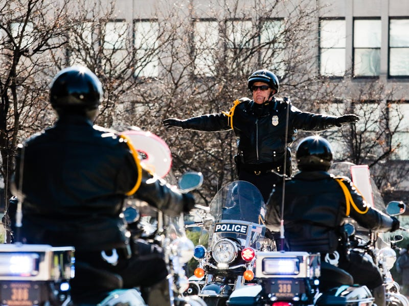 A motorcade officer stands on top of his motorcycle with outstretched arms during the Veterans Day Parade on Saturday.