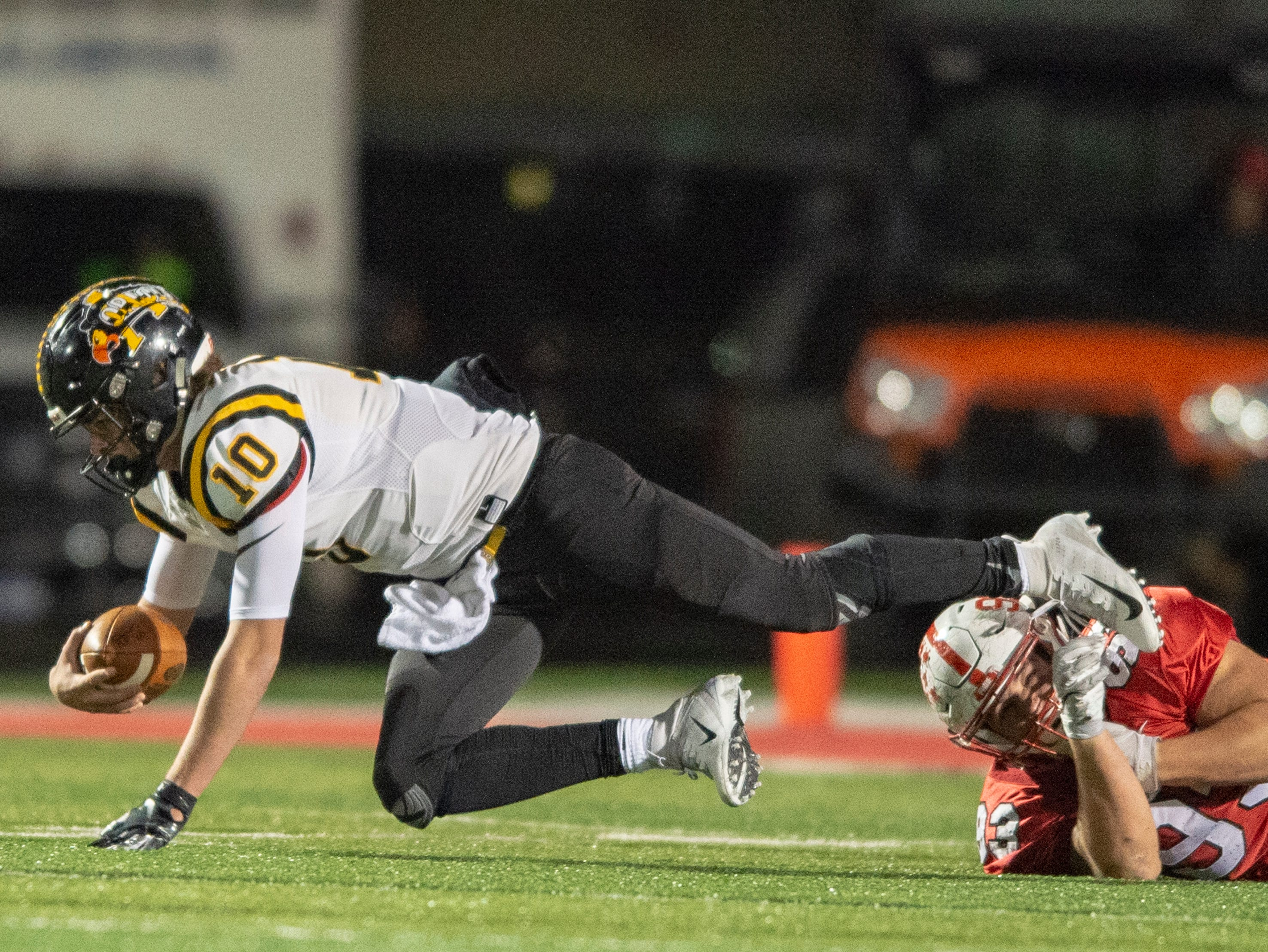 Avon High School sophomore Henry Hesson (10) is tripped up by Center Grove High School senior Lucas Hunter (93) during the first half of action. Center Grove High School hosted Avon High School in an IHSAA Class 6A Regional Championship varsity football game, Friday, Nov. 9, 2018.
