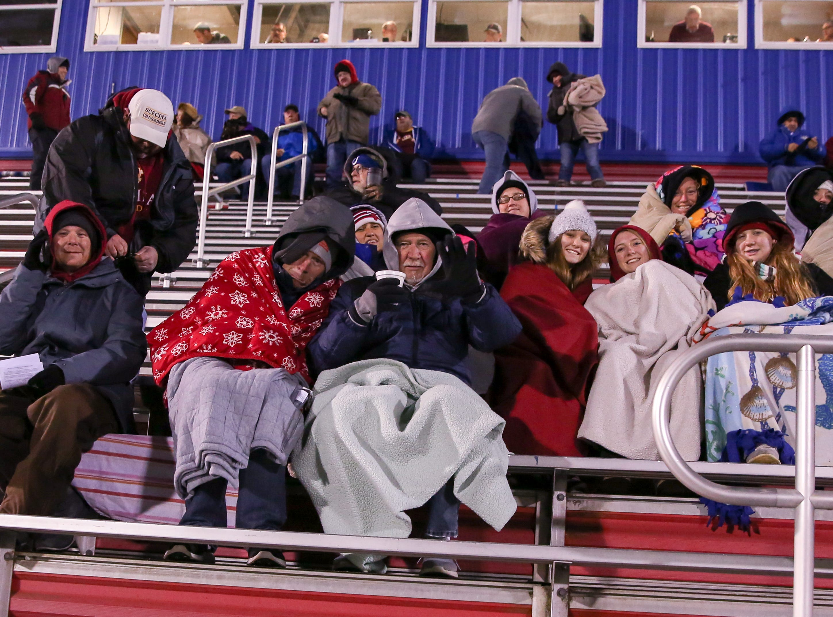Fans try to stay warm waiting for the start of Indianapolis Scecina vs Western Boone High School varsity football in the Class 2A Regional Championship held at Roncalli High School, Friday, November 9, 2018.