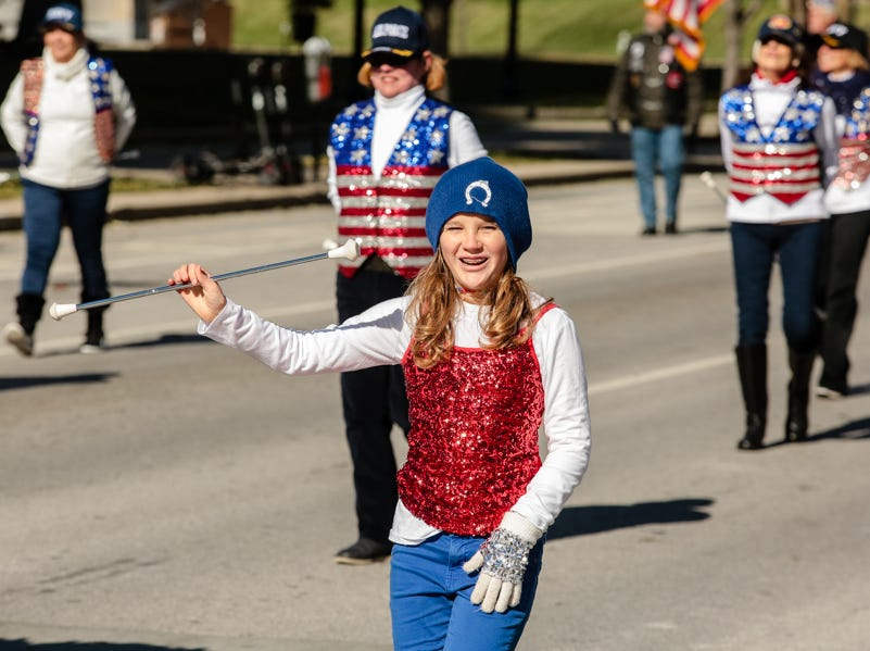 A kid walks in the Veterans Day Parade.