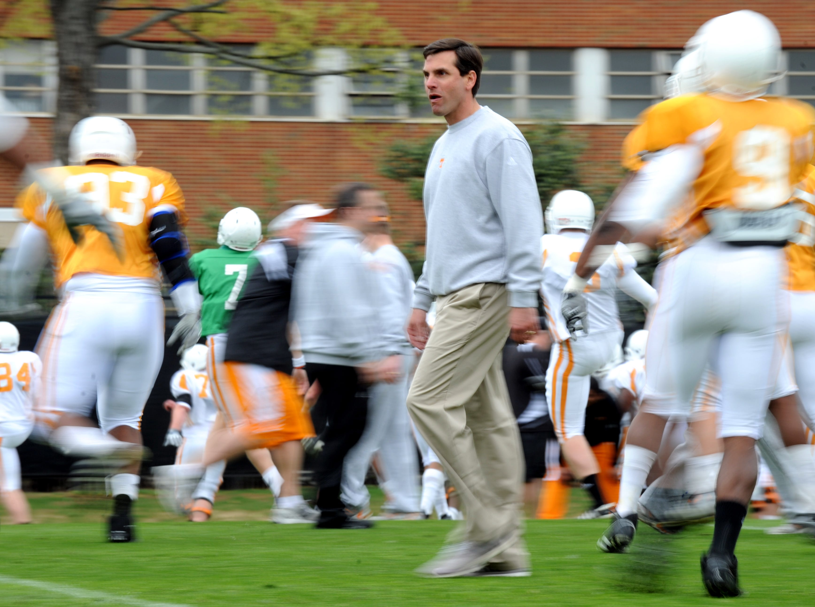 Tennessee head coach Derek Dooley walks across the field as his team warms up during practice at Haslam Field on campus Saturday, March 26, 2011.