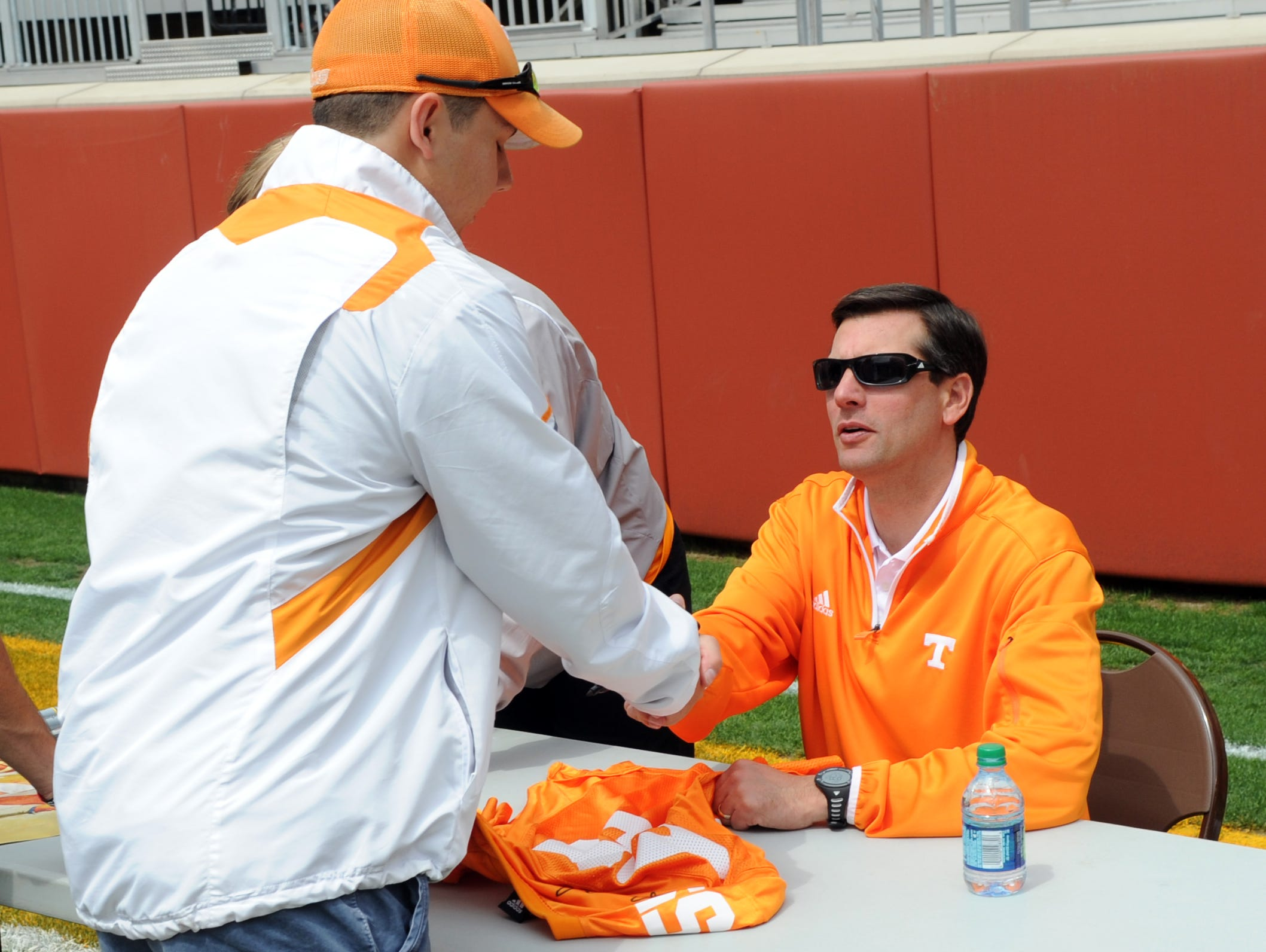 Tennessee head coach Derek Dooley shakes hands with Corey Blevins from Jasper, Tenn., during Fan Day prior to the Orange and White Game at Neyland Stadium Saturday, April 21, 2012.