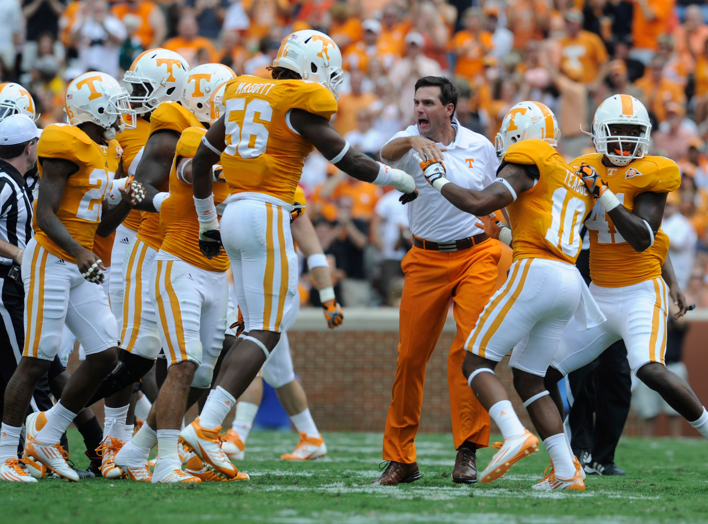 Tennessee head coach Derek Dooley celebrates with the team after they held Cincinnati on a fourth down at Neyland Stadium Saturday, Sept. 10, 2011.