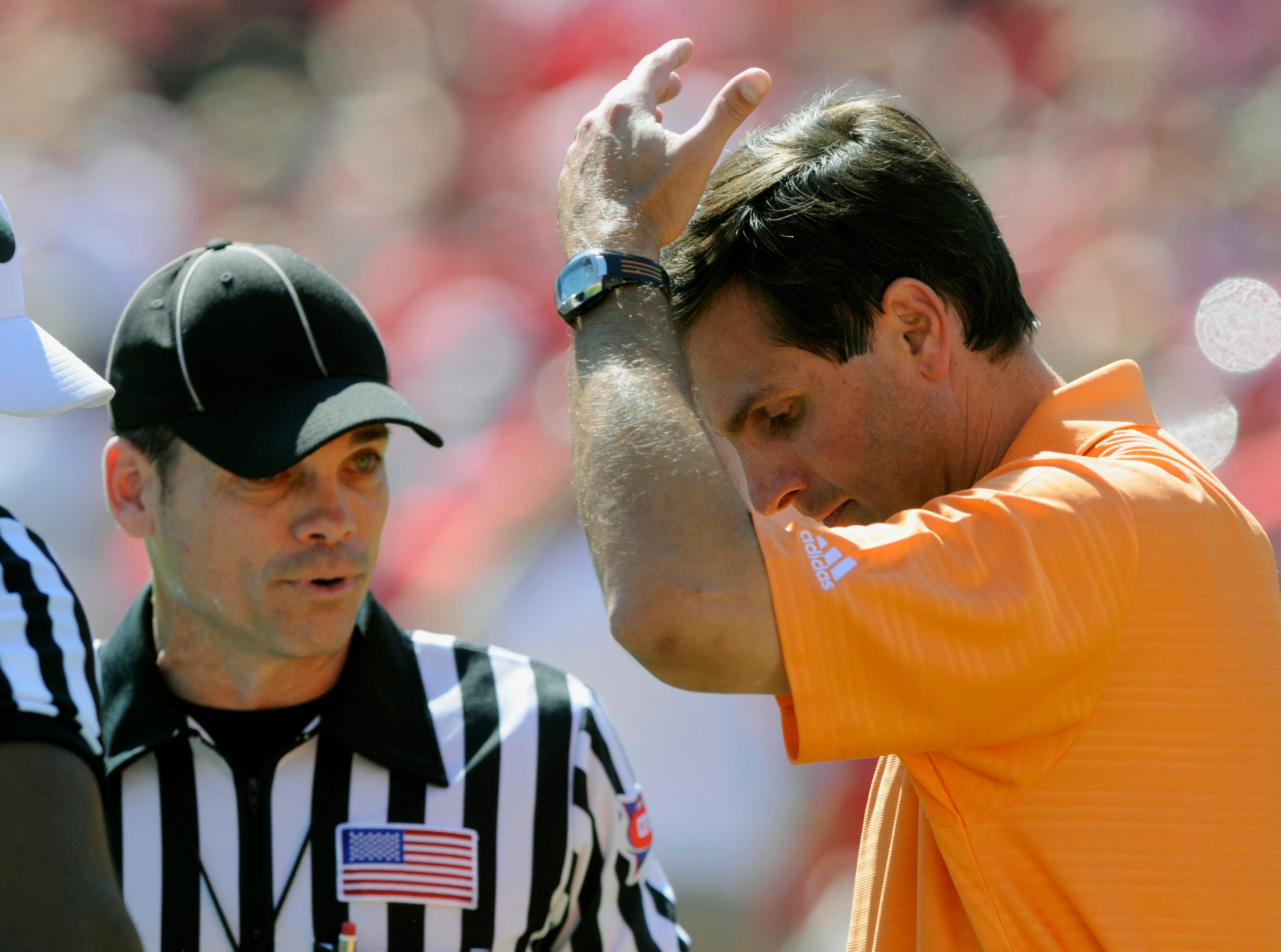 Tennessee head coach Derek Dooley listens to a call form the referee during the second half Saturday, Oct. 9, 2010 in Sanford Stadium in Athens, GA.