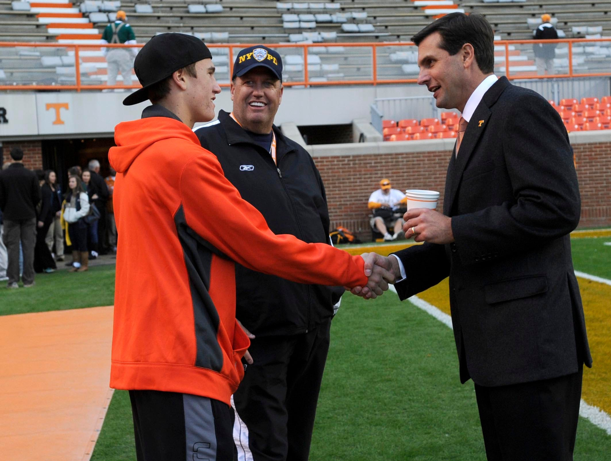 Tennessee head coach Derek Dooley, right, greets New York Jets head coach Rex Ryan, center and his son, Seth Ryan, as they attend the South Carolina game as part of a recruiting visit at Neyland Stadium on Saturday, Oct. 29, 2011.