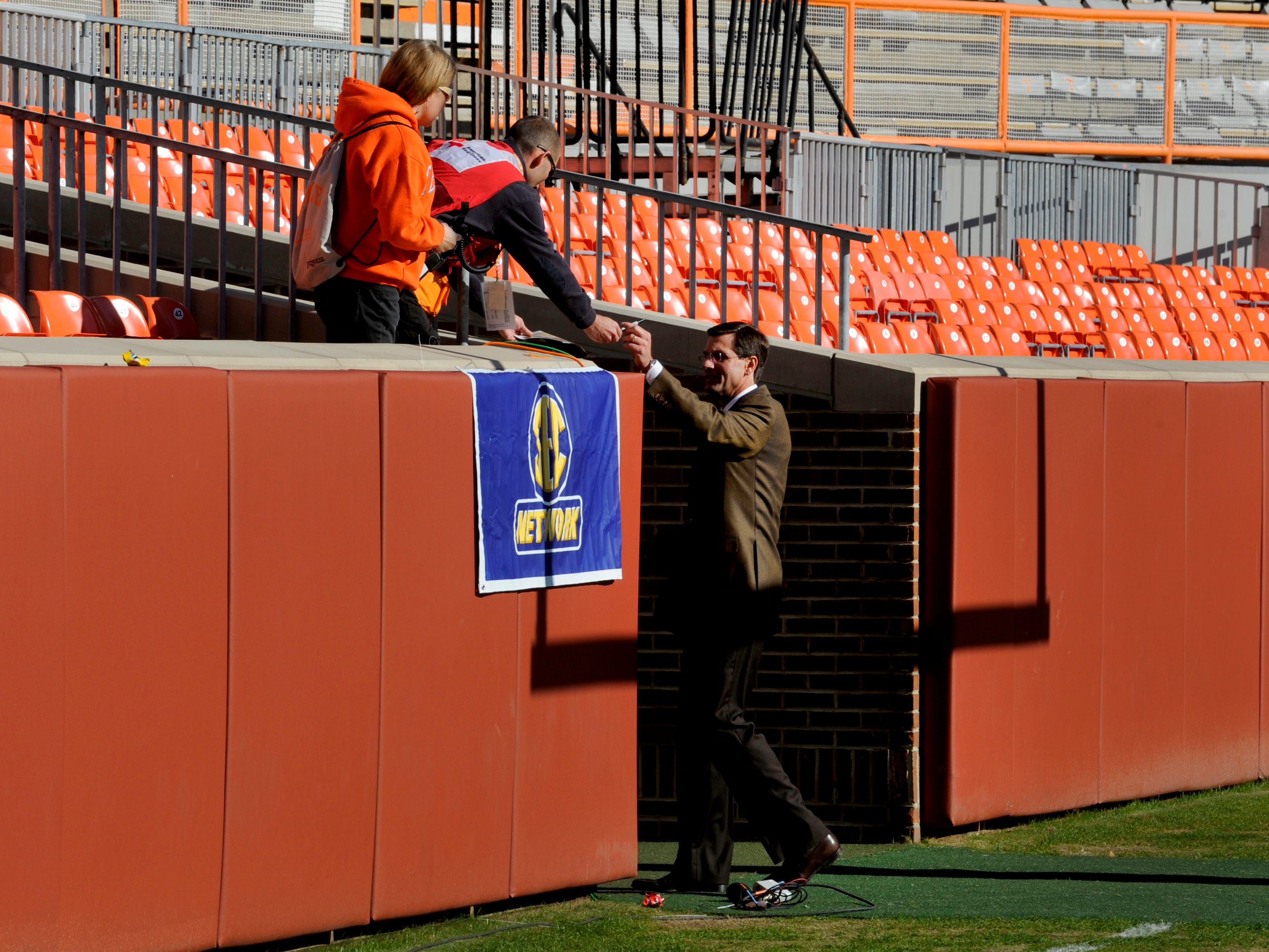 Tennessee head coach Derek Dooley signs an autograph for a fan during his pre game walk around the field prior to their game against Missouri at Neyland Stadium Saturday, Nov. 10, 2012.