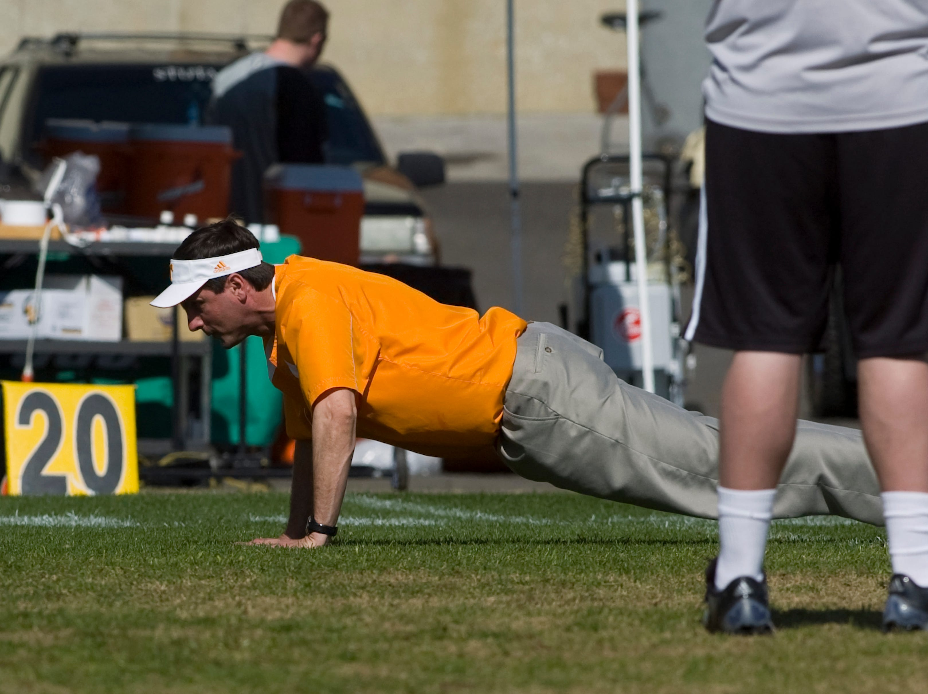 Tennessee head coach Derek Dooley does push ups during football practice at Haslam Field on Wednesday, Mar. 31, 2010