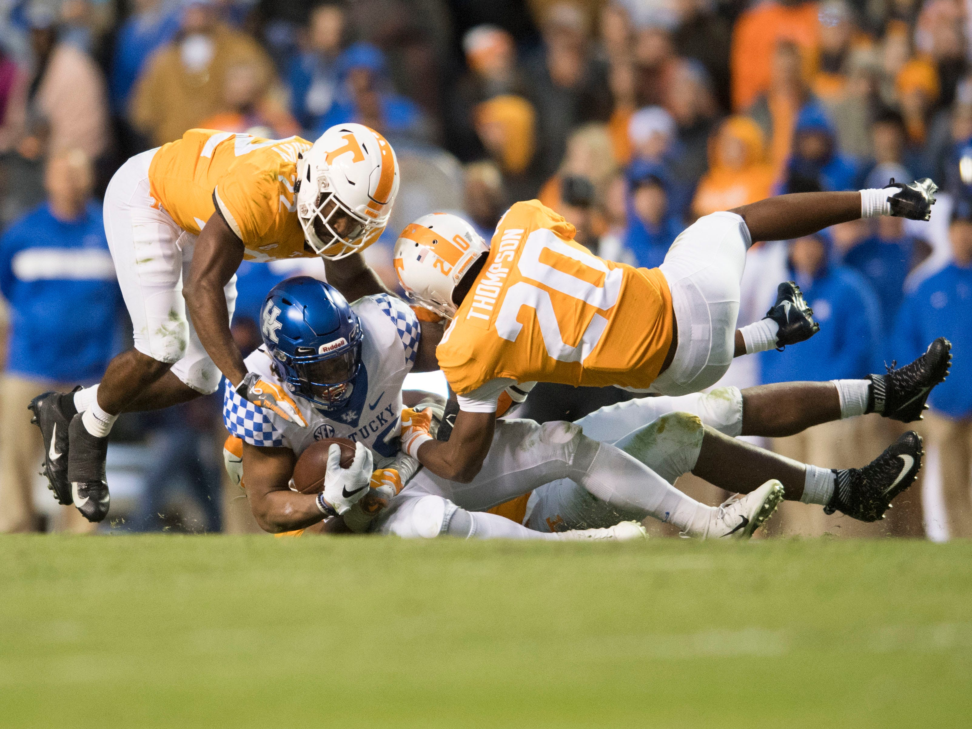Kentucky running back Benny Snell Jr. (26) goes down under Tennessee defensive backa Micah Abernathy (22) and Bryce Thompson (20) during a game between Tennessee and Kentucky at Neyland Stadium in Knoxville, Tennessee on Saturday, November 10, 2018.
