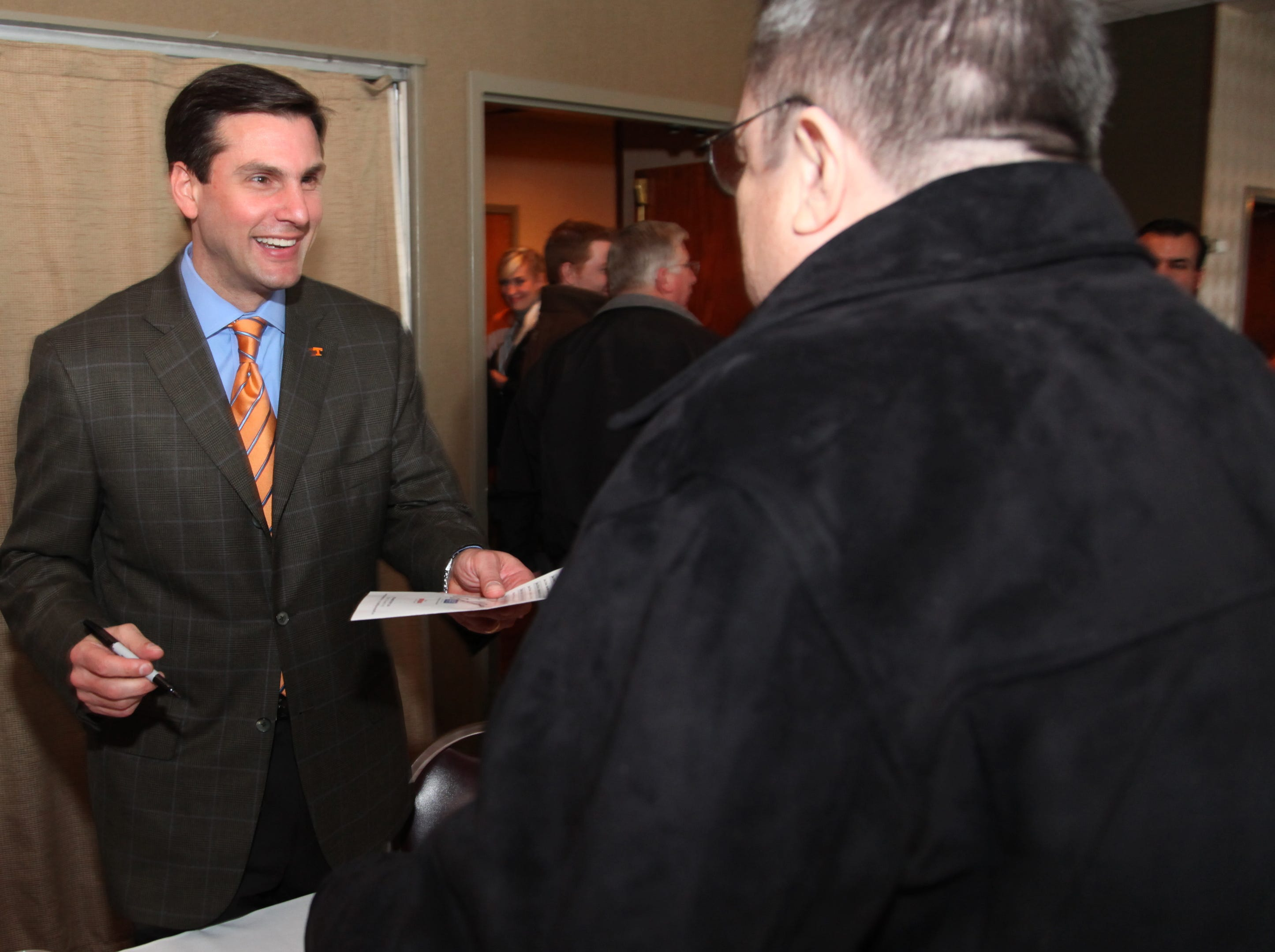 Tennessee football coach Derek Dooley, left, signs an autograph for Jerry Campbell following the Big Orange Tip-off Club meeting at Calhoun's restaurant Wednesday, Feb. 24, 2010.