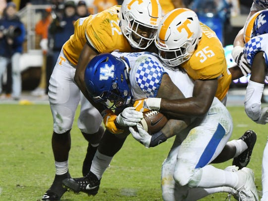 Tennessee defensive back Micah Abernathy (22) and  linebacker Daniel Bituli (35) take down Kentucky running back Benny Snell Jr. (26) during first half action in the Kentucky game Saturday, November 10, 2018 at Neyland Stadium in Knoxville, Tenn.