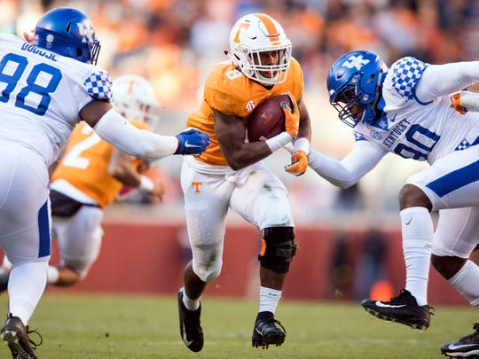 Tennessee running back Ty Chandler (8) gets through Kentucky defensive tackle Tymere Dubose (98) and  defensive end T.J. Carter (90) during a game between Tennessee and Kentucky at Neyland Stadium in Knoxville, Tennessee on Saturday, November 10, 2018.