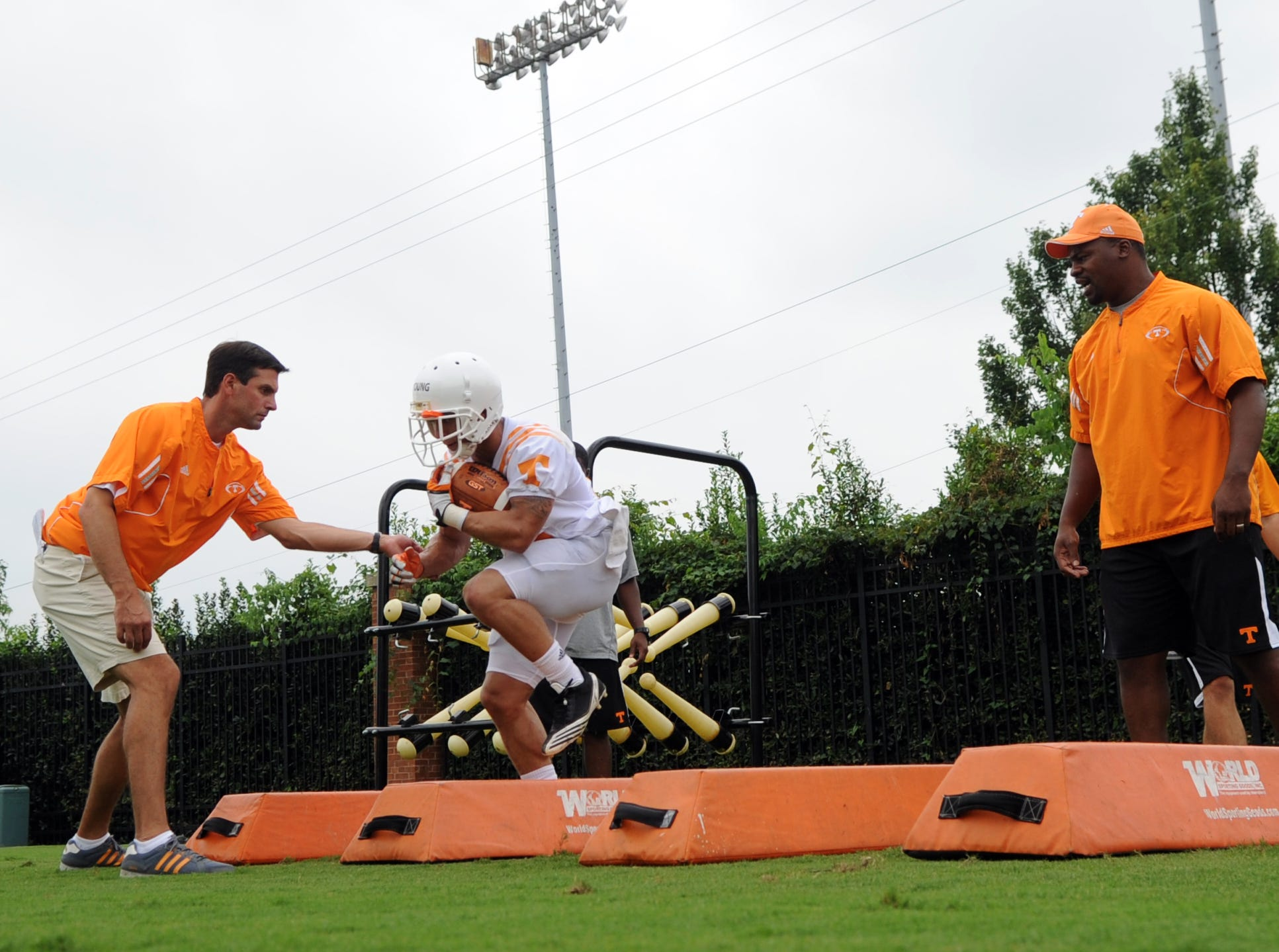 Tennessee head coach Derek Dooley helps tailback Devrin Young as he runs a drill under the supervision of running backs coach Jay Graham, right, during practice at Haslam Field at the University of Tennessee Friday, Aug. 3, 2012.