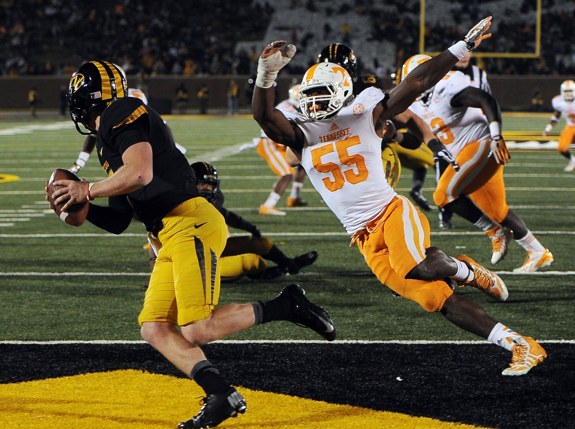Missouri quarterback Maty Mauk, left, scrambles away from Tennessee defensive lineman Jacques Smith (55) during the second half of an NCAA college football game Saturday, Nov. 2, 2013, in Columbia, Mo.