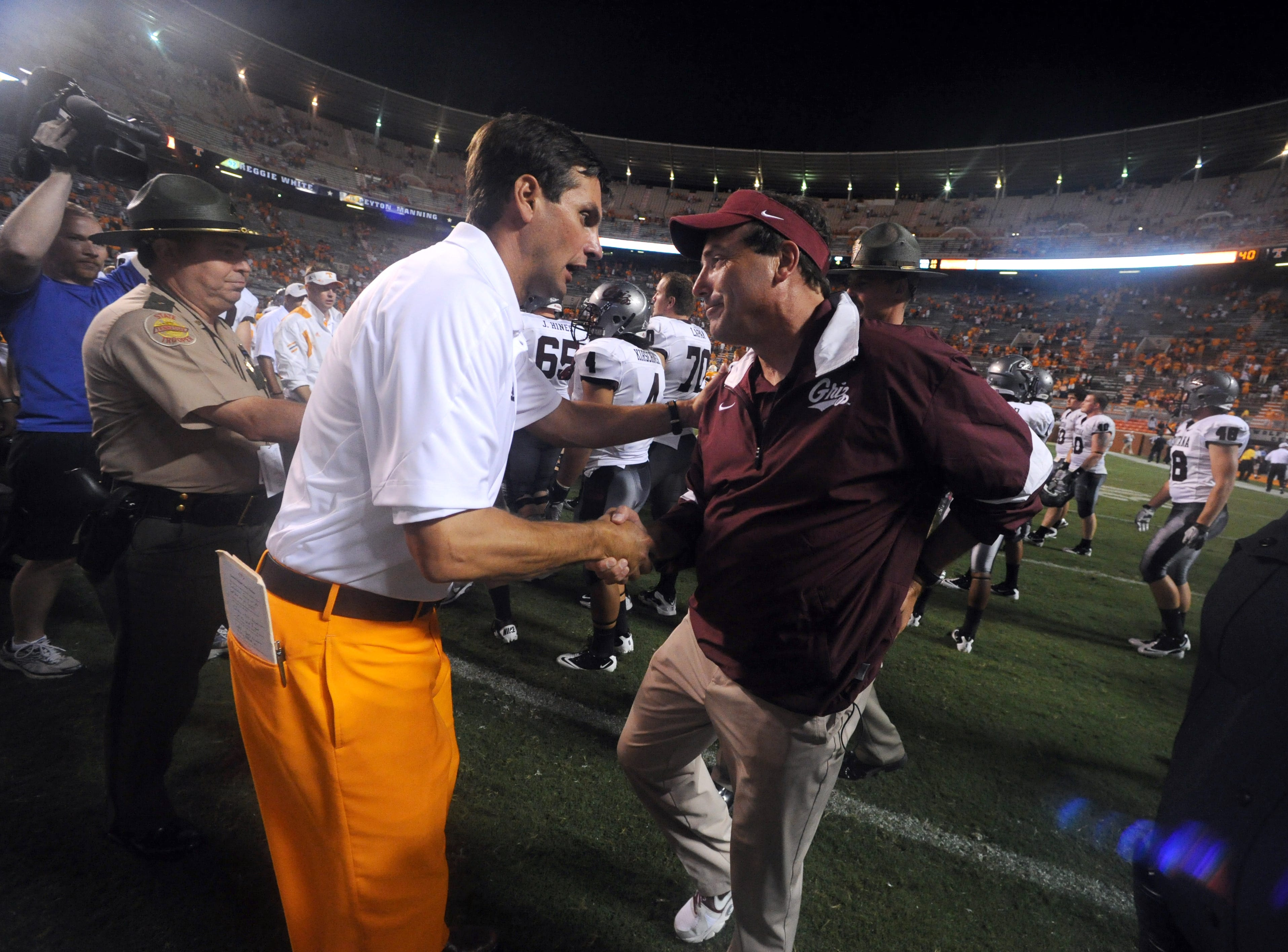 Tennessee head coach Derek Dooley, left, shakes hands with Montana head coach Robin Pflugrad, right, after the Vols defeated the Grizzlies 42-16 at Neyland Stadium Saturday, Sept. 3, 2011.