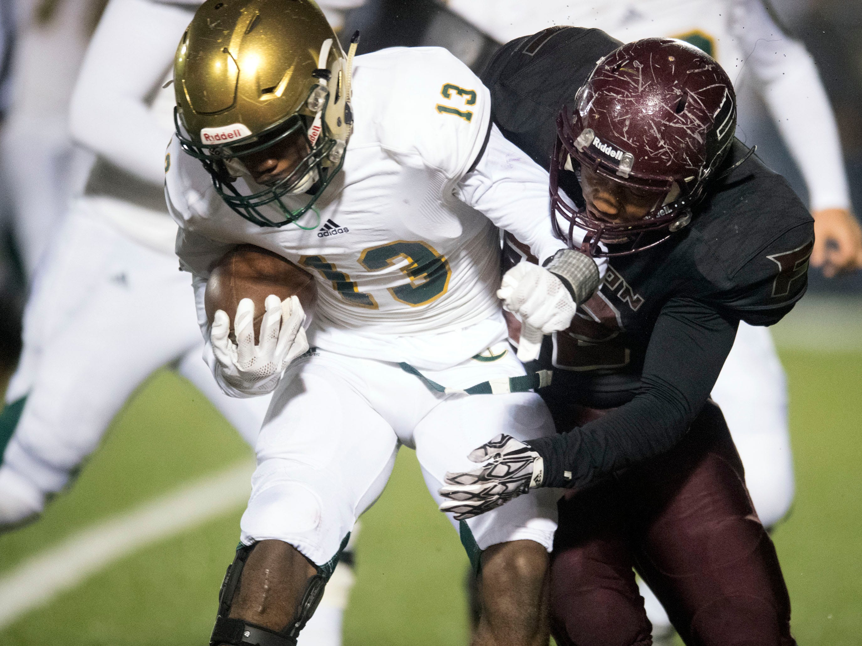 Knoxville Catholic's Ray Thompson (13) is stopped by Fulton's Terrence Brown (22). Knoxville Catholic beat Fulton, 28-25 in the second round of the Class 5A playoffs on Friday, November 9, 2018.