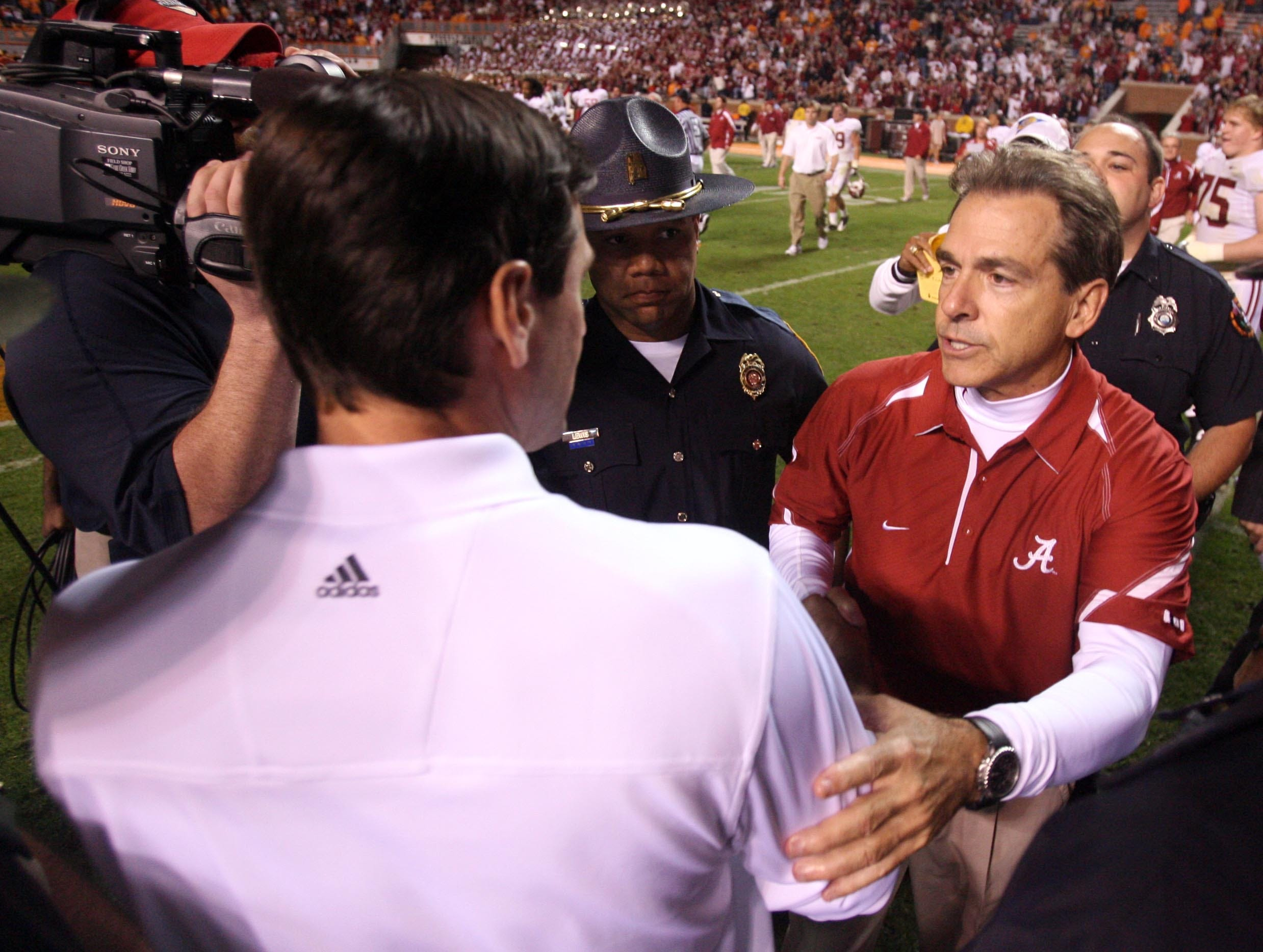 Tennessee head coach Derek Dooley, left, shakes hands with Alabama head coach Nick Saban after the Vols' 41-10 loss to the Crimson Tide at Neyland Stadium Saturday, Oct. 23, 2010.