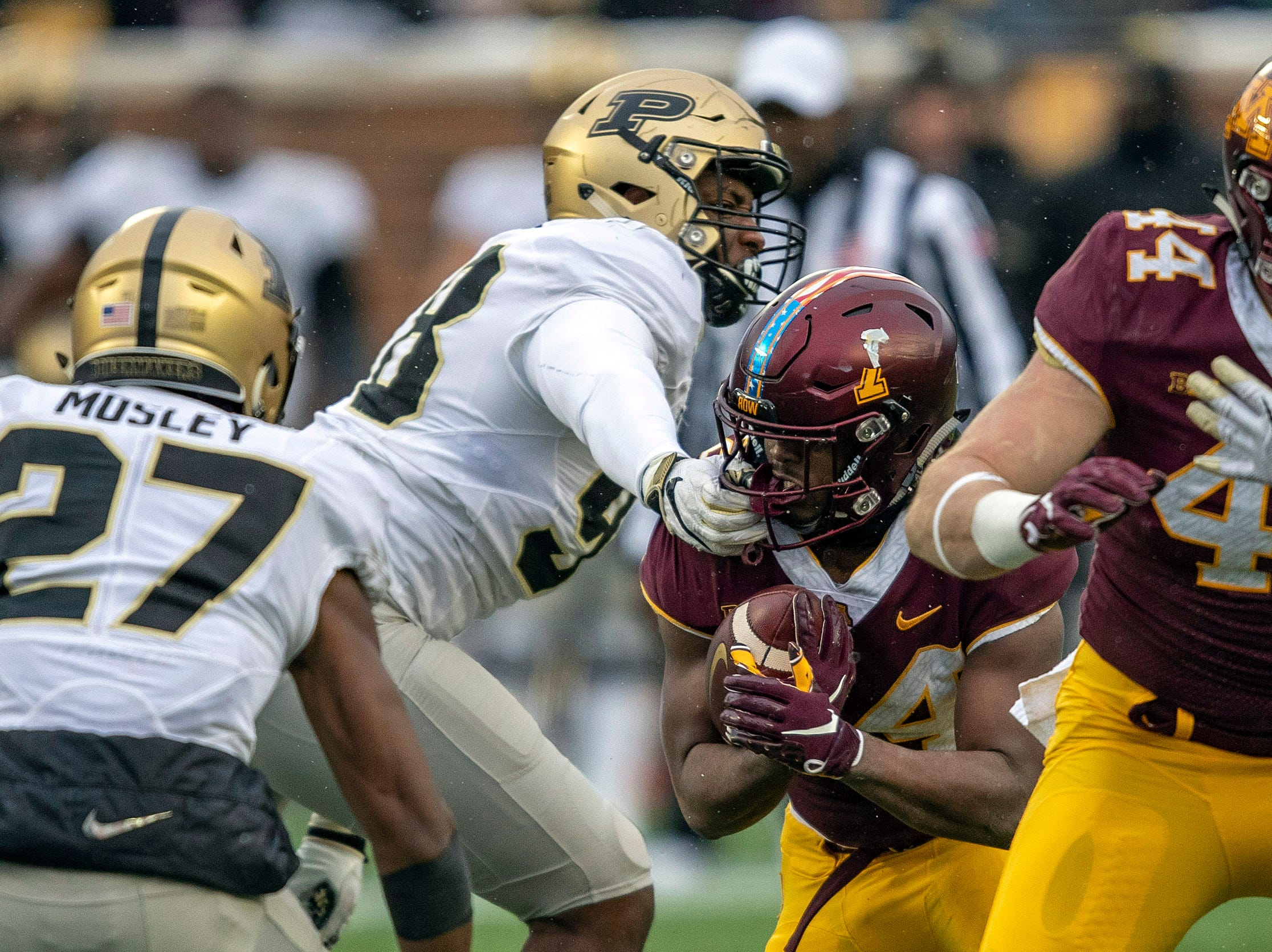 Nov 10, 2018; Minneapolis, MN, USA; Purdue Boilermakers defensive end Kai Higgins (98) grabs Minnesota Golden Gophers running back Mohamed Ibrahim (24) face mask during the first half at TCF Bank Stadium. Mandatory Credit: Jesse Johnson-USA TODAY Sports
