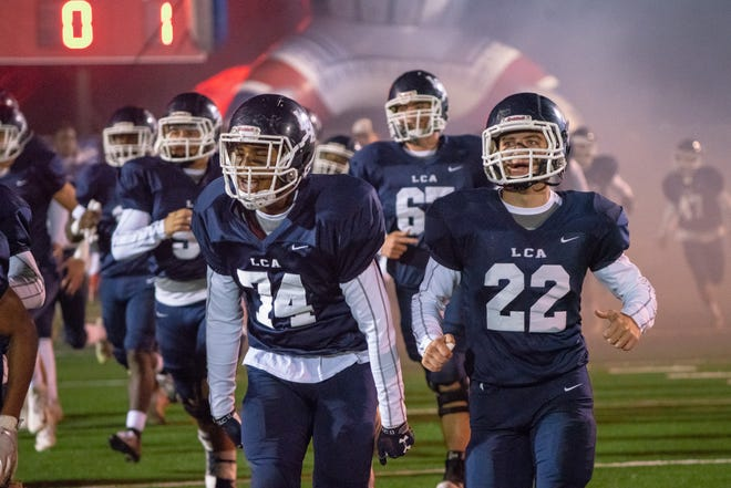 The Lafayette Christian Academy Knights run onto the field as they take on the Houma Christian Warriors at Clark Field in the first round of the high school football playoffs Friday Nov. 9, 2018.