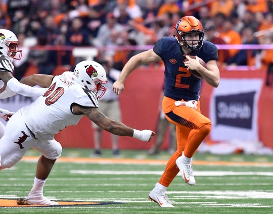 Eric Dungey (2) runs the ball past Louisville's Jared Goldwire (90) in Friday's win.