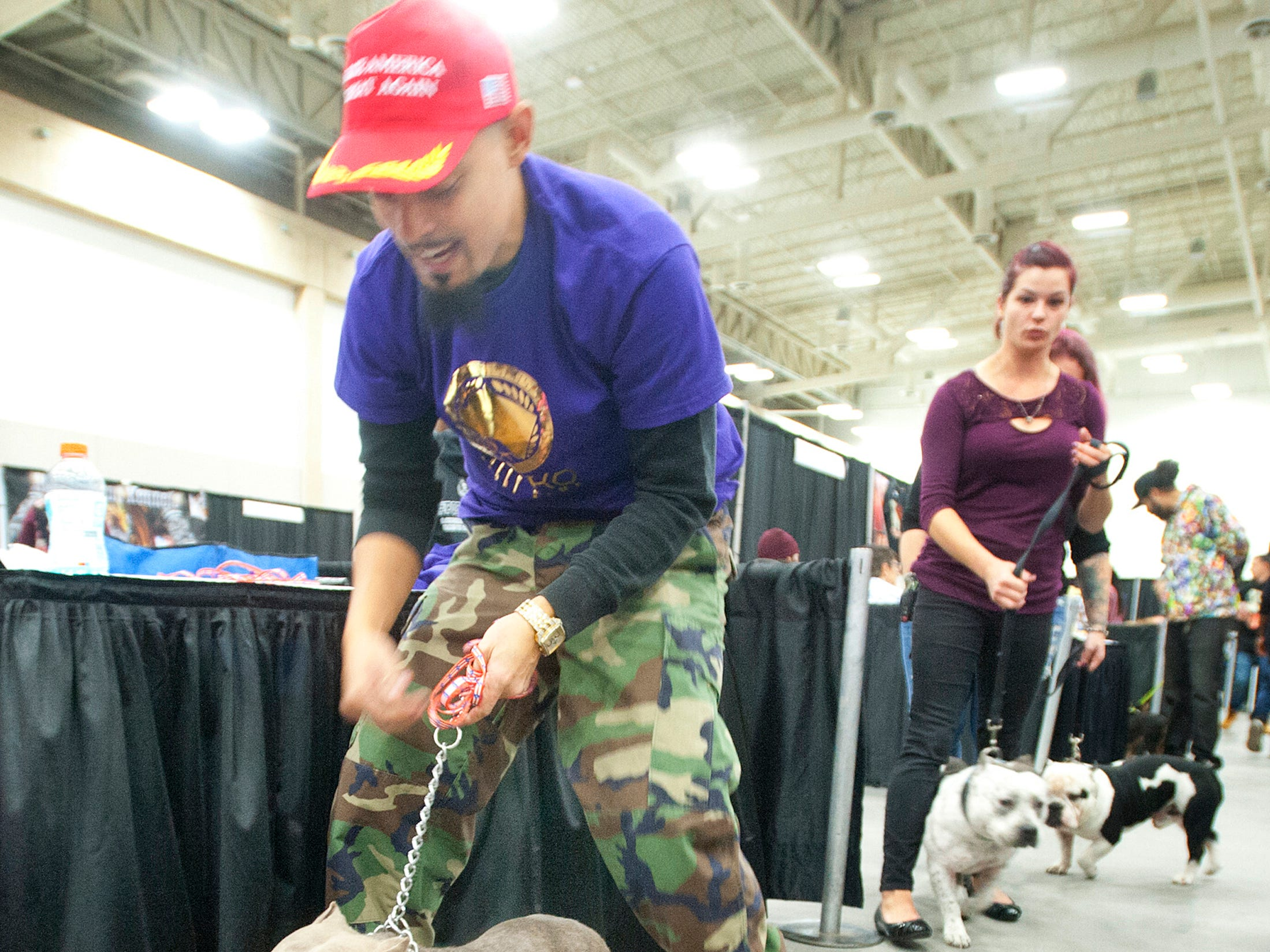 Daniel Lleras of Radcliffe, Ky., holds onto GrekoBully Kamp as the two get their photo taken at the 2018 American Bully Kennel Club's 12th annual confirmation event at the Kentucky Convention Center in Louisville.November 10, 2018
