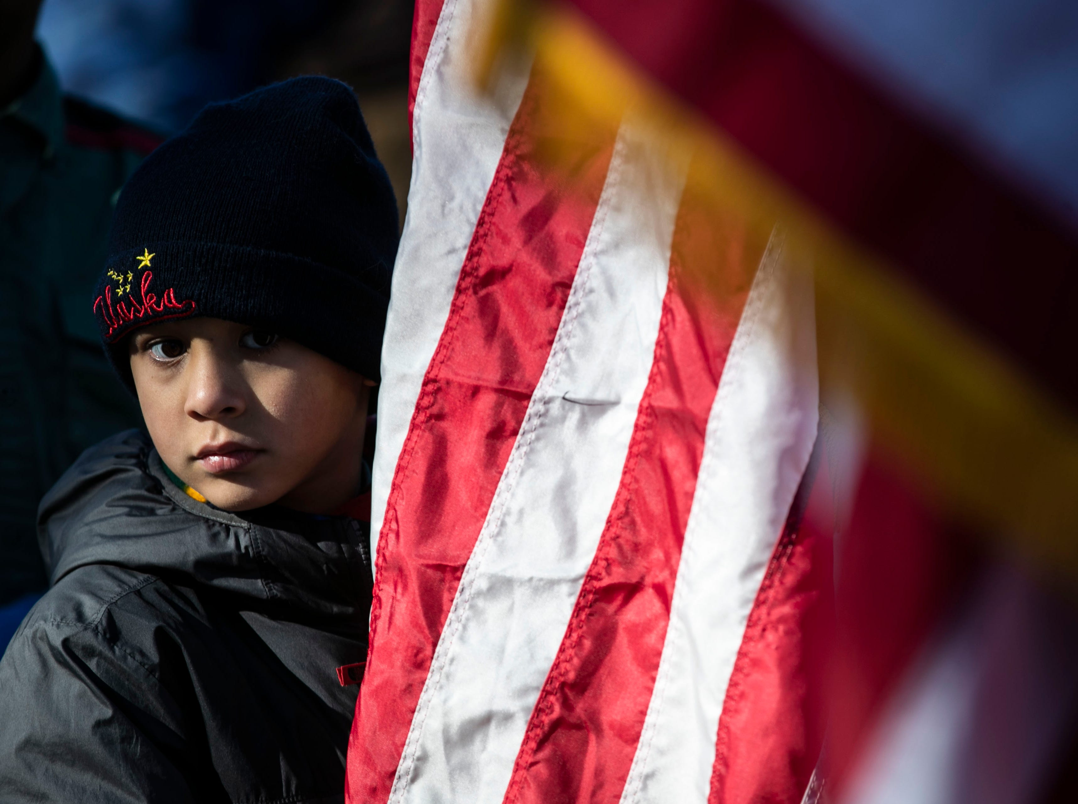 Jake Romero peers around an American flag before a short walk to Cave Hill Cemetery as a remembrance to military veterans during a Flags 4 Vets event Saturday, Nov. 10, 2018. Veterans Day is Sunday, Nov. 11. Around 250 volunteers placed nearly 7,500 flags on military veteran gravesites.