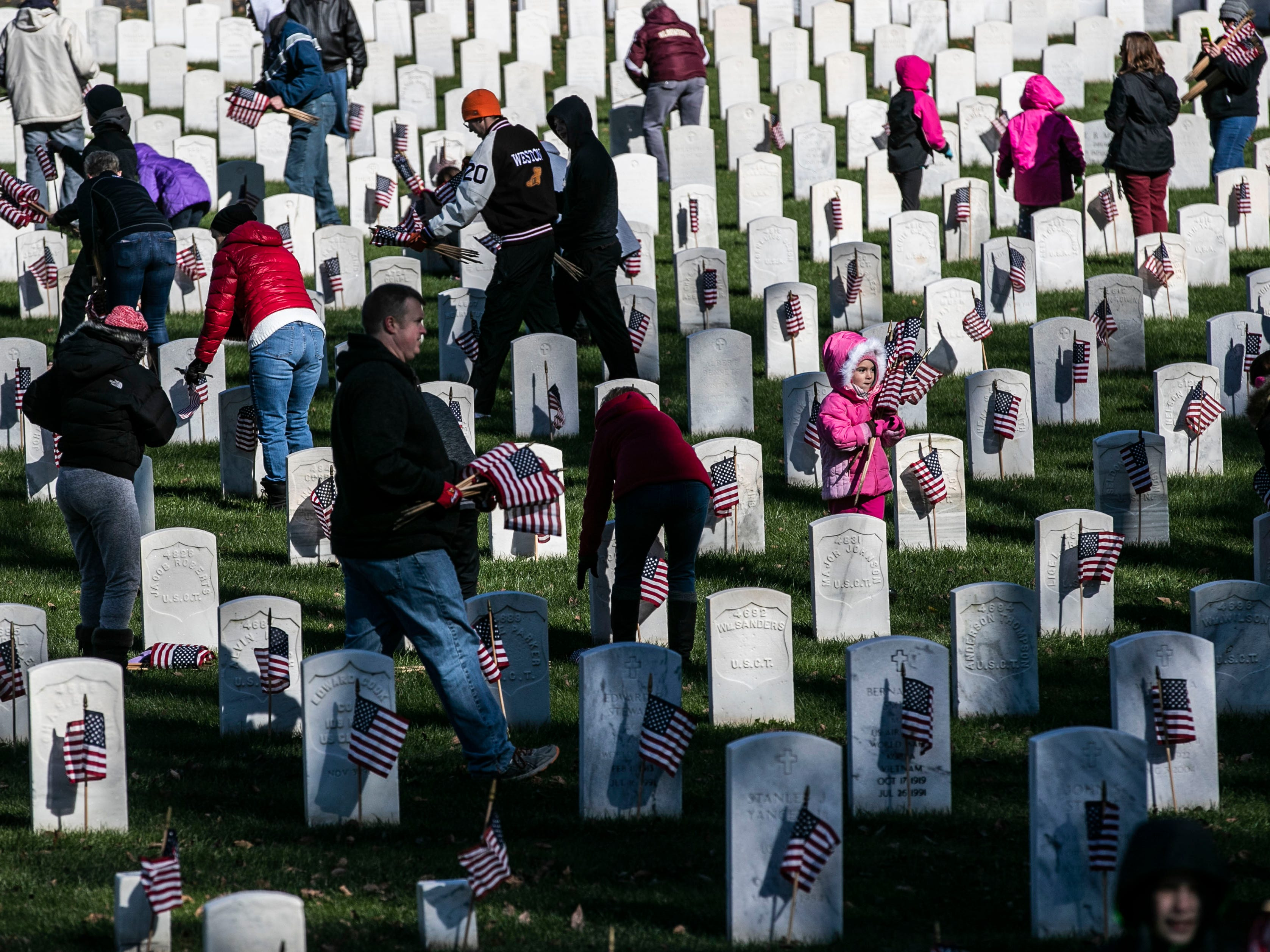 Adults and children placed small American flags as a remembrance to military veterans buried at Cave Hill Cemetery during a Flags 4 Vets event Saturday, Nov. 10, 2018. Veterans Day is Sunday, Nov. 11. Around 250 volunteers placed nearly 7,500 flags on military veteran gravesites.