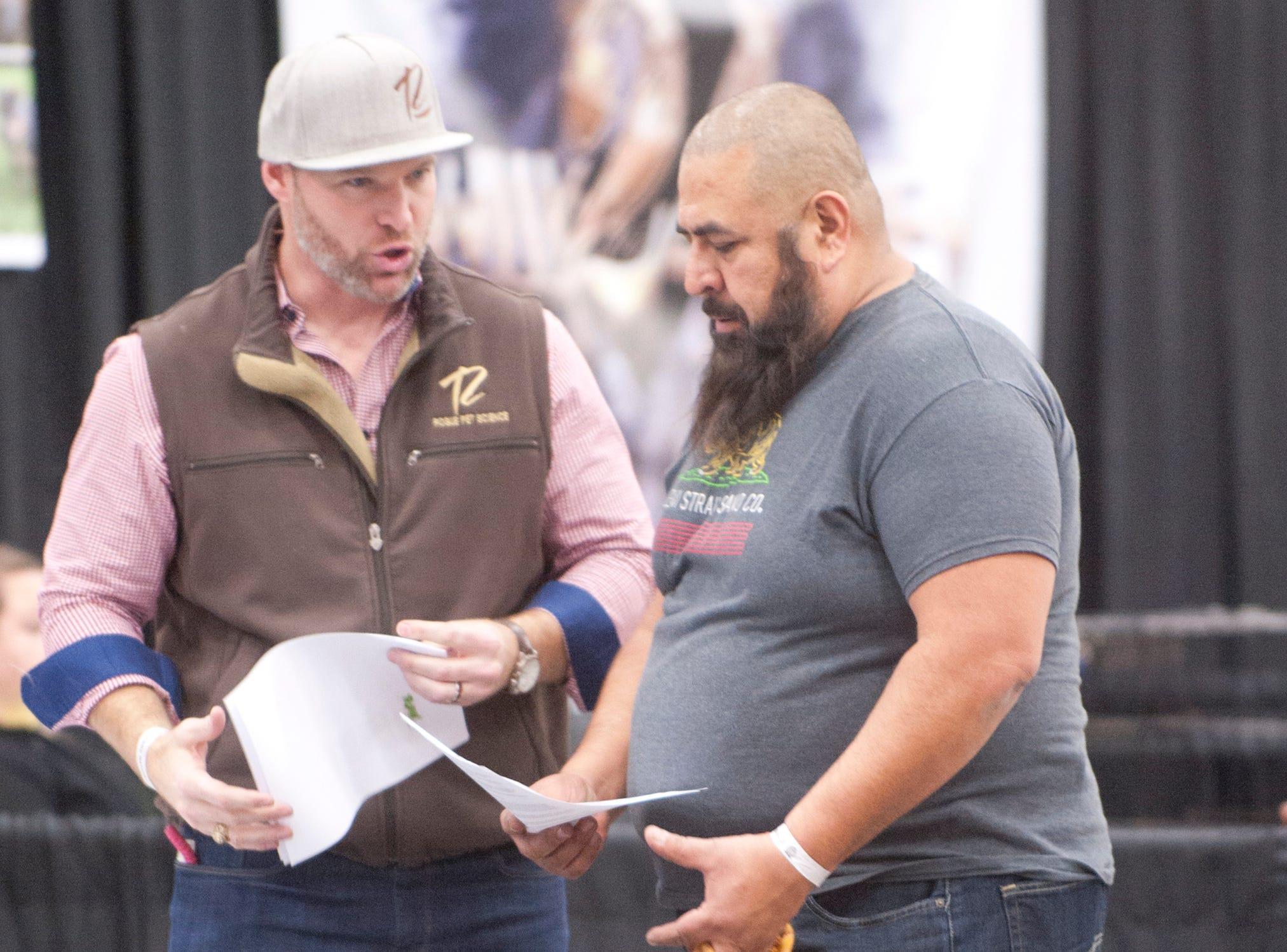 Jesu Torres, of Indianapolis, right, holding onto his dog, Kai, chats with Nathan Dewsbury, left, scientist and founder of Rogue Pet nutrition food, at the 2018 American Bully Kennel Club's 12th annual confirmation event at the Kentucky Convention Center in Louisville. Torres is looking for a new food to help him grow his dog and Dewsbury has a new food developed for carnivores.November 10, 2018