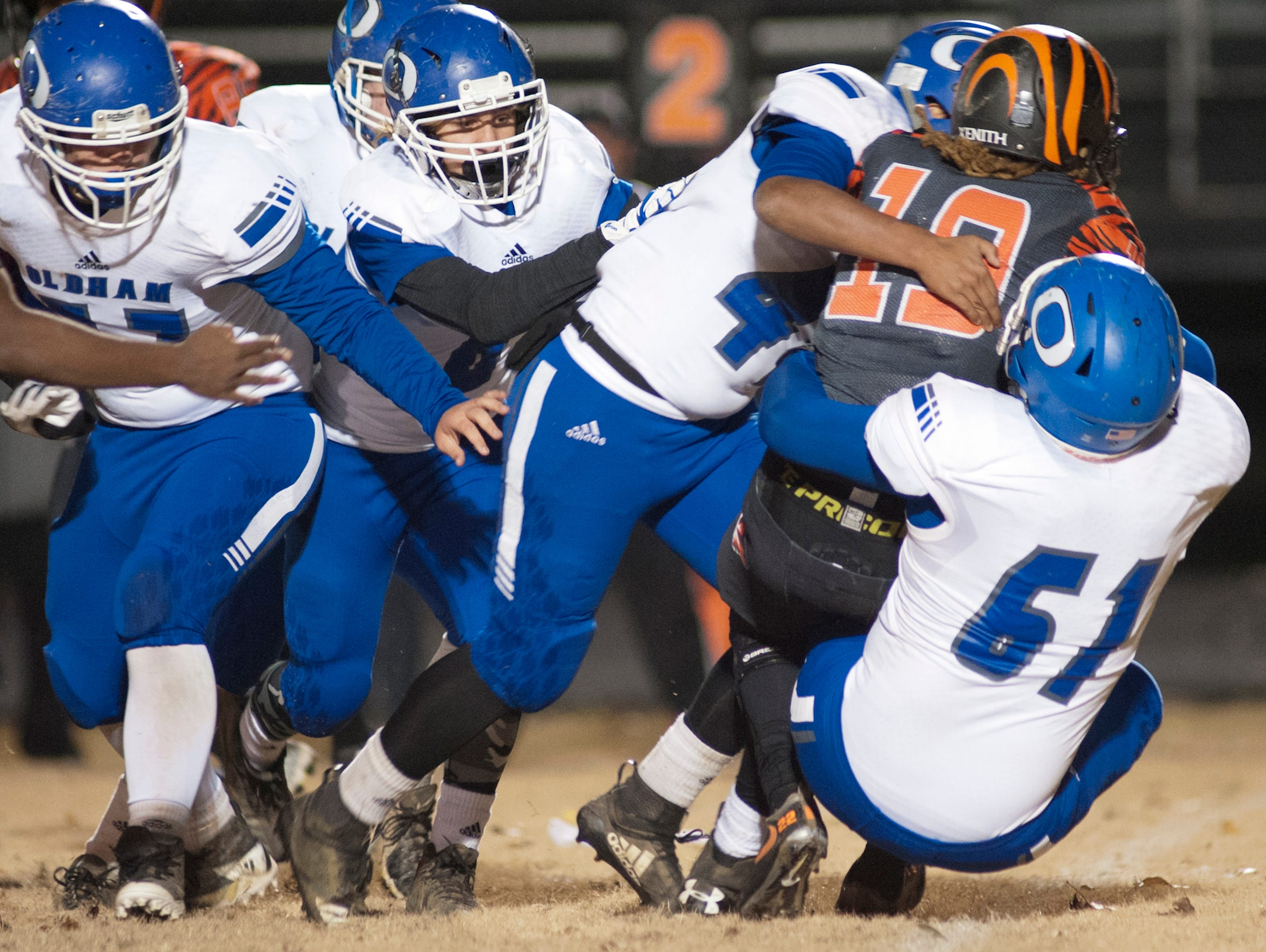 The Oldham County defense, led by  Oldham County defensive lineman Deven Cancel, right, brings down Fern Creek running back Anthony Teague. Nov. 9, 2018