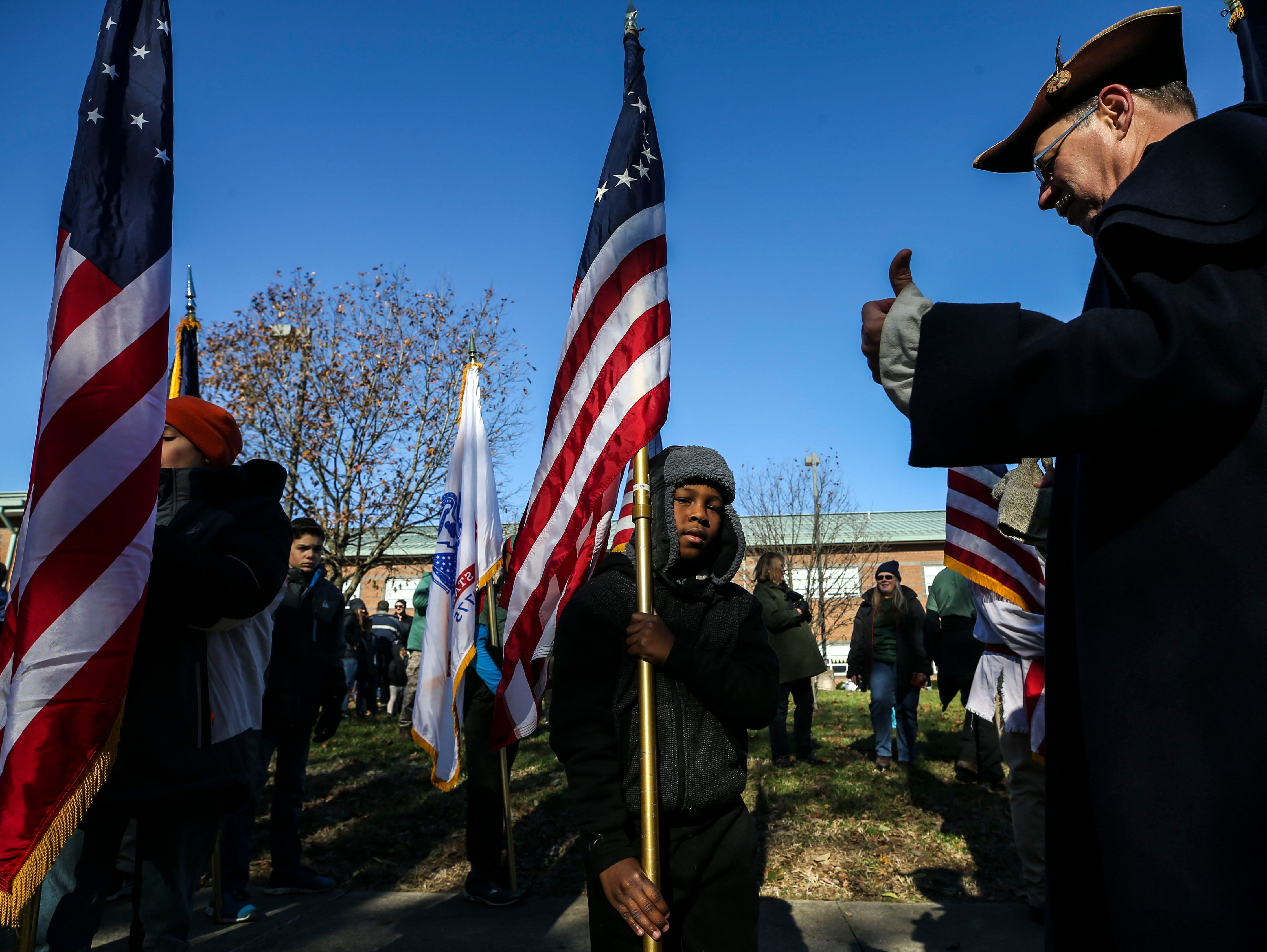 Larry Selpy, right gives Trail Life scout Xander Roberts, 8, some tips on how to carry and plant the flag as the two wait during the Flags 4 Vets ceremony at Cave Hill Cemetery Saturday morning.
