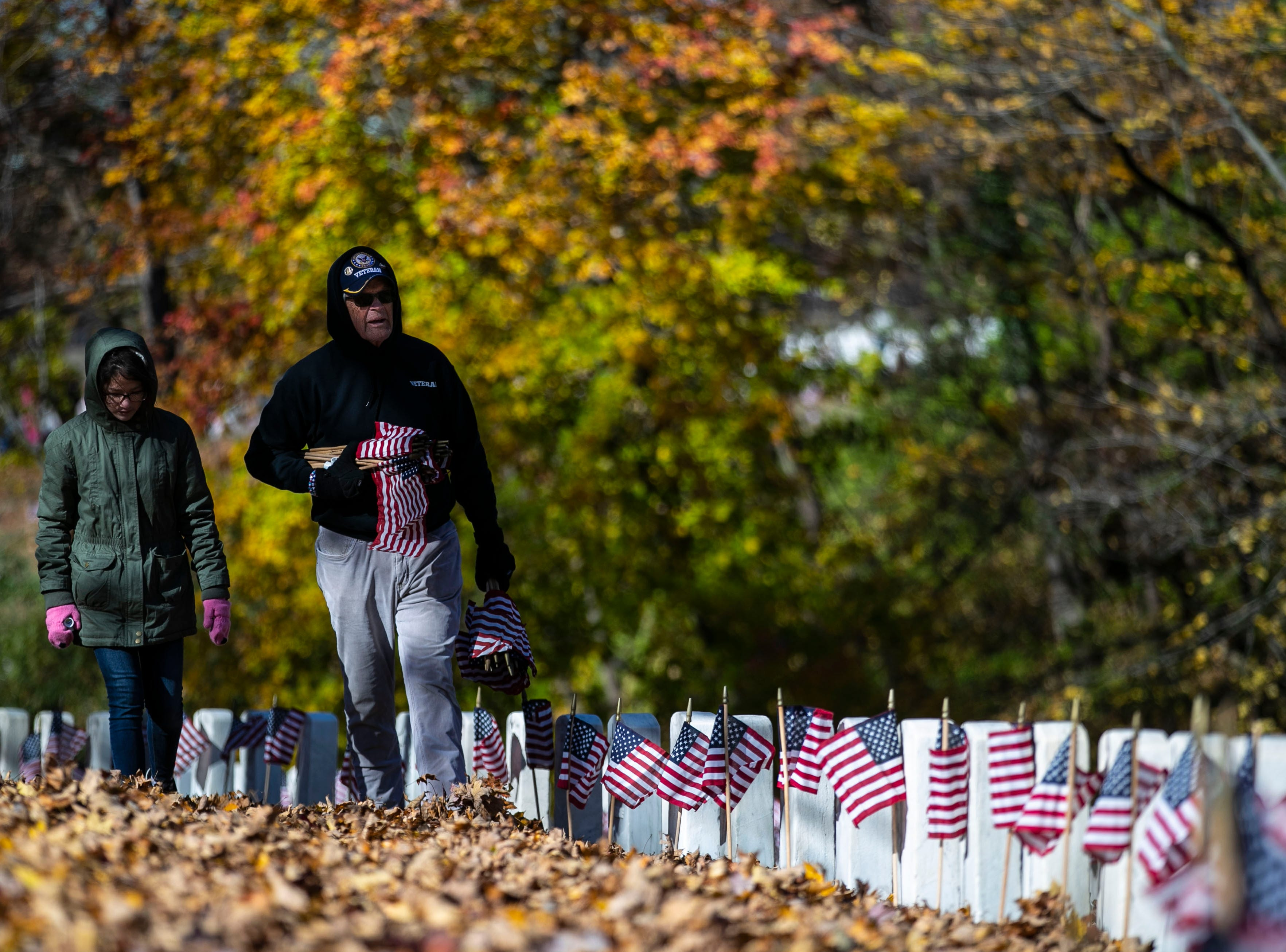 Mia Tichy walks through the fallen leaves while grandfather and Vietnam War veteran Bob Tichy carries flags to place during a Flags 4 Vets event at Cave Hill Cemetery Saturday, Nov. 10, 2018. Veterans Day is Sunday, Nov. 11. Around 250 volunteers placed nearly 7,500 flags on military veteran gravesites.